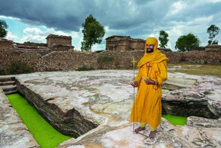 Monk Mikael, holding a pilgrim's cross, stands by two of the hand-cut rock cisterns that capture enough water during the rains to last the community the entire year.
