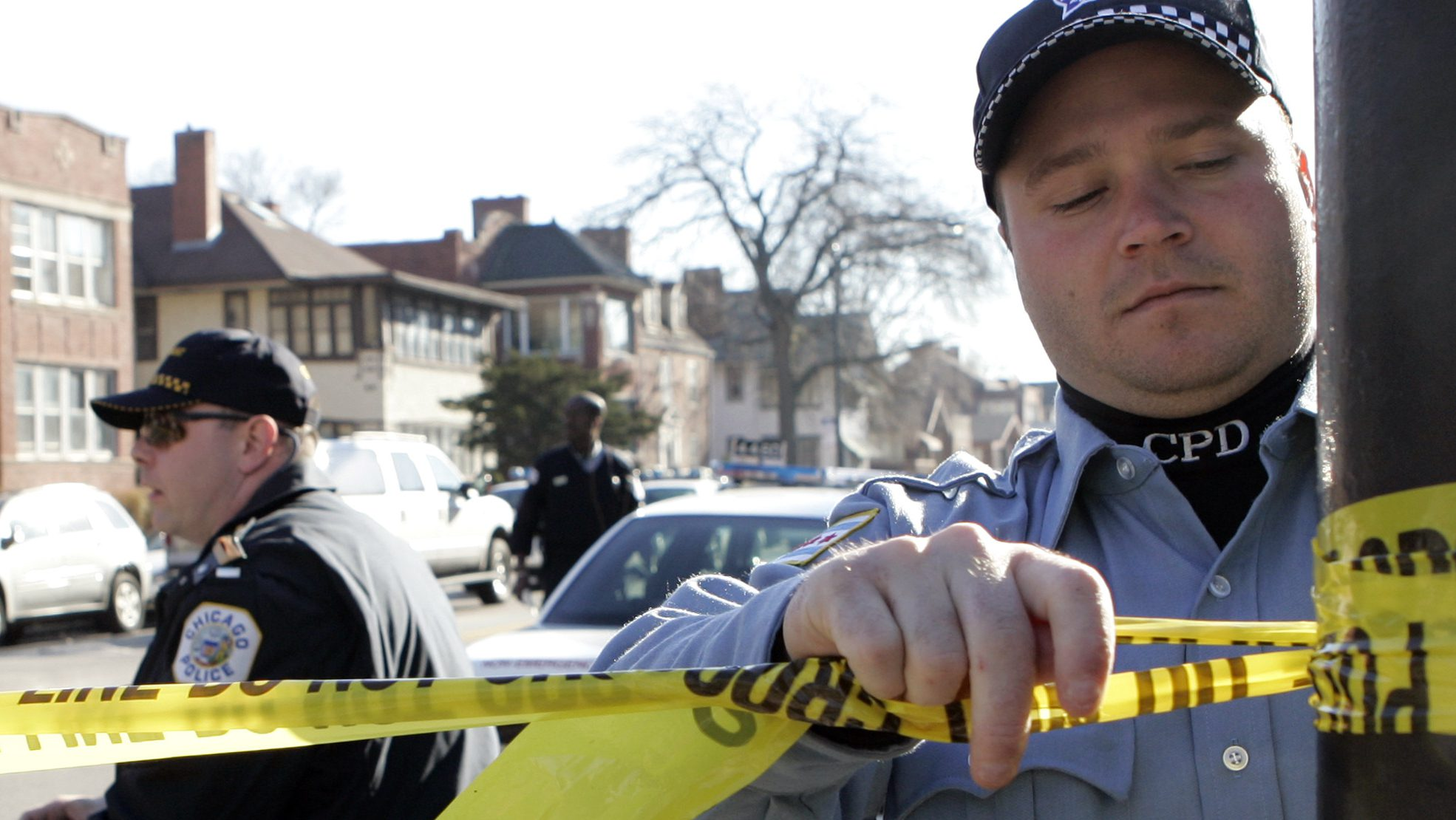 Chicago Police official re-taped a police line at apartment standoff, Thursday, Nov. 23, 2006, in Chicago. Two women were taken hostage inside their Chicago apartment building early Thursday, sparking a police standoff that stretched more than 10 hours on Thanksgiving.(AP Photo/Nam Y. Huh)