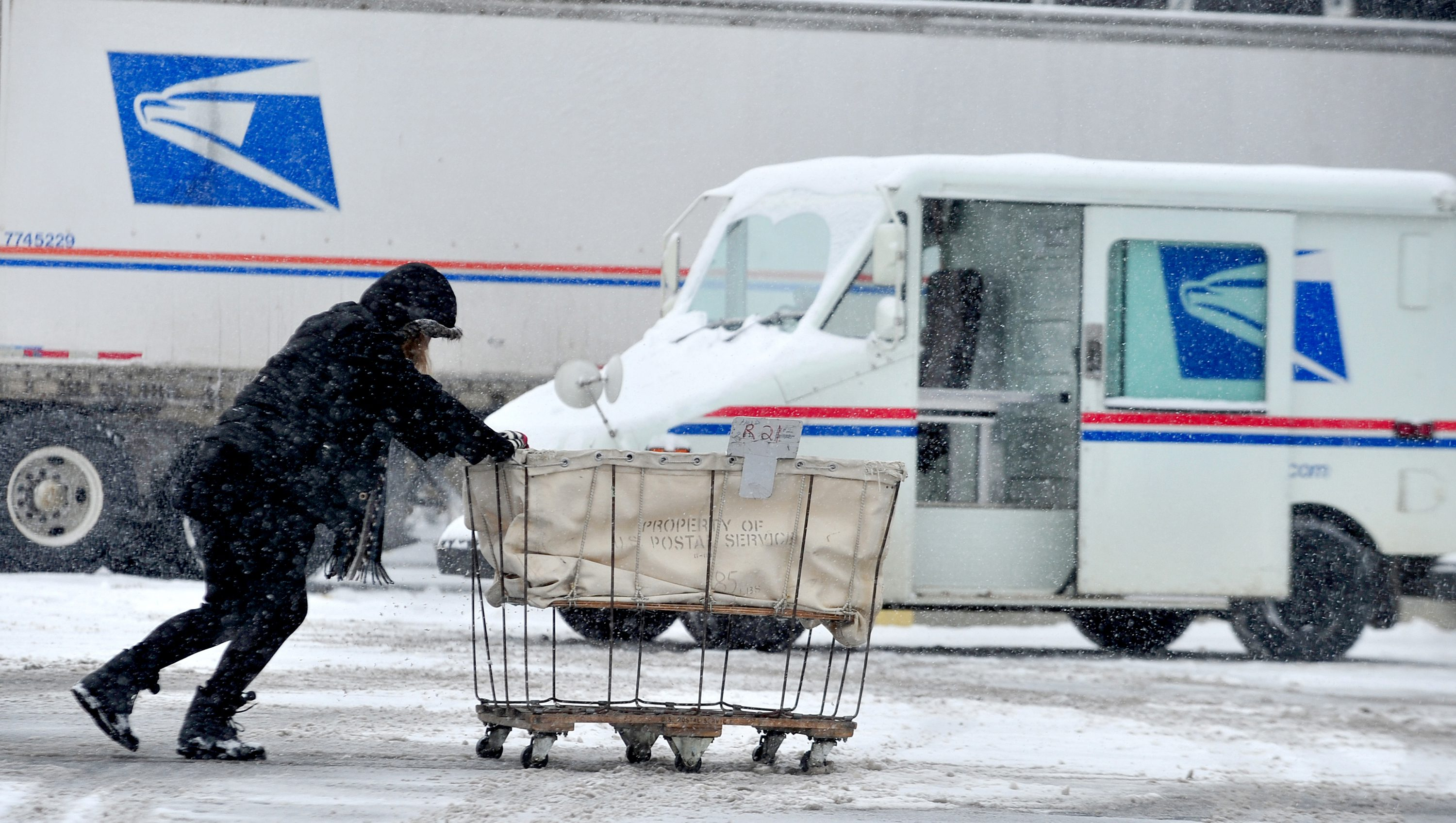 USPS Carrier Stephanie Starr, Of Seymour, Pushes A Mail Cart From Her  Carrier Vehicle