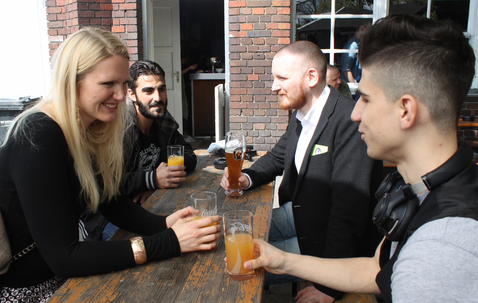 In this May 1, 2016 photo Cindy Spieker, Ahmed Haj Ali, Paul Spieker and Abdul Wahab, from left, sit around a table in Berlin. The group met through a website called 'Let's integrate!' that sets dates between refugees and locals in Berlin.