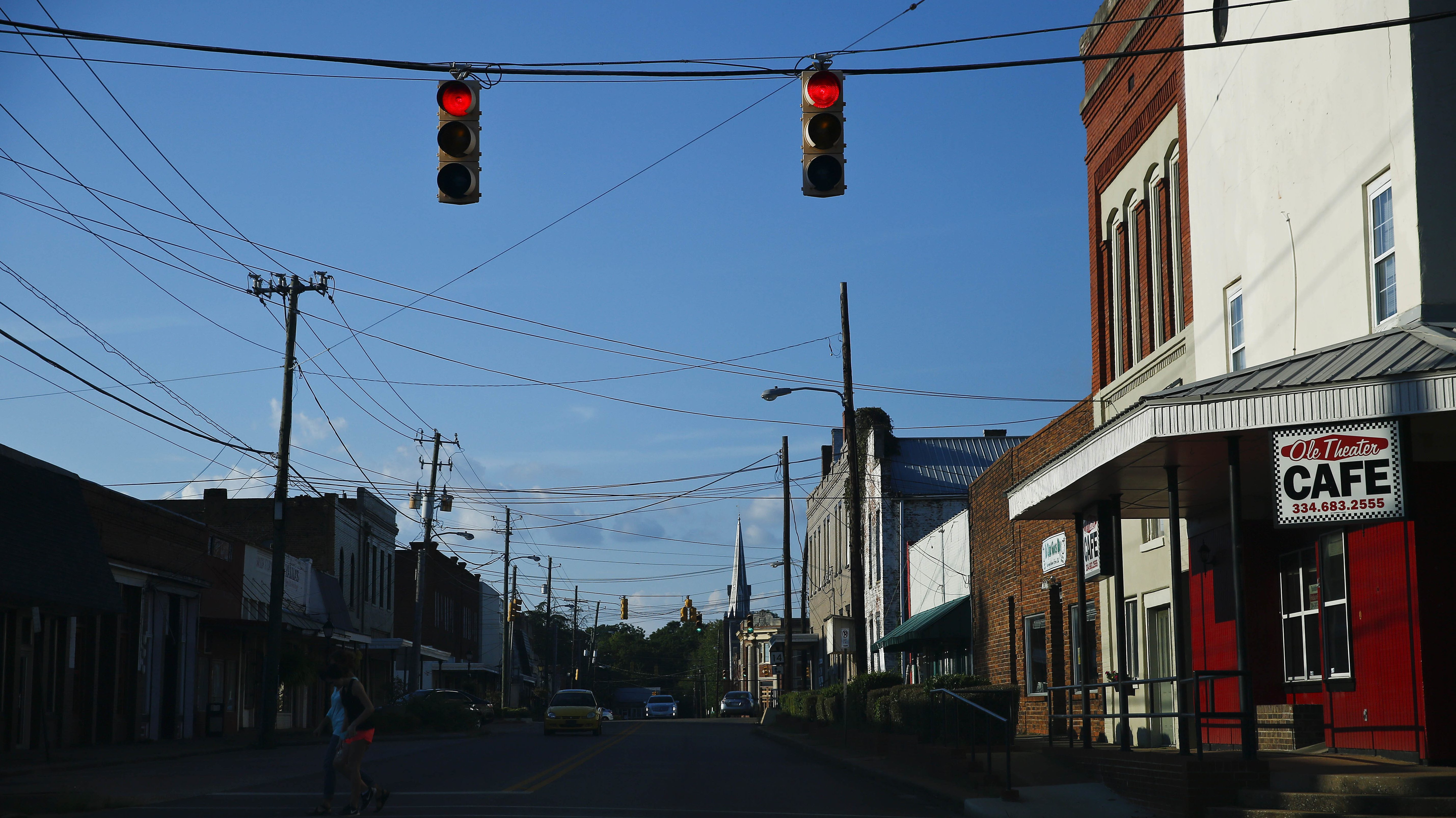 Two residents cross one of the main streets in downtown Marion, Ala., Wednesday, Aug. 24, 2016. Stretching from east Texas to southern Virginia, the impoverished area known as the Black Belt is heavily populated by blacks who supported Barack Obama. Now, many worry about President Donald Trump, echoing fears of other black Americans. (AP Photo/Brynn Anderson)