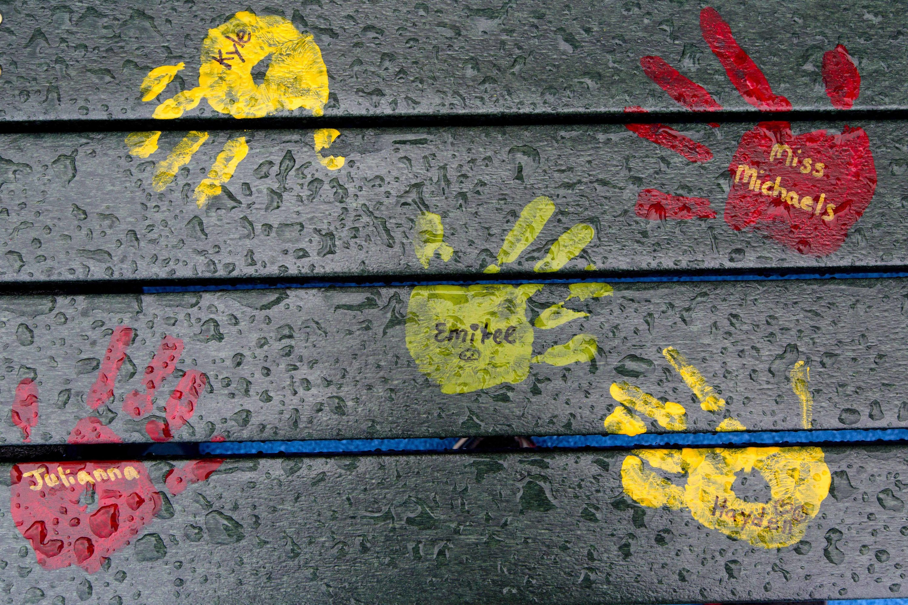 In this July 29, 2016 file photo, painted hand prints with names of teachers and students are on a playground bench at the new Sandy Hook Elementary School in Newtown, Conn. Students attended the first day of classes there on Monday, Aug. 29, 2016. The new building replaced the one that was demolished where 20 first graders and six educators were shot and killed in December 2012. The names on the bench are not those of people killed in the 2012 massacre at the school.