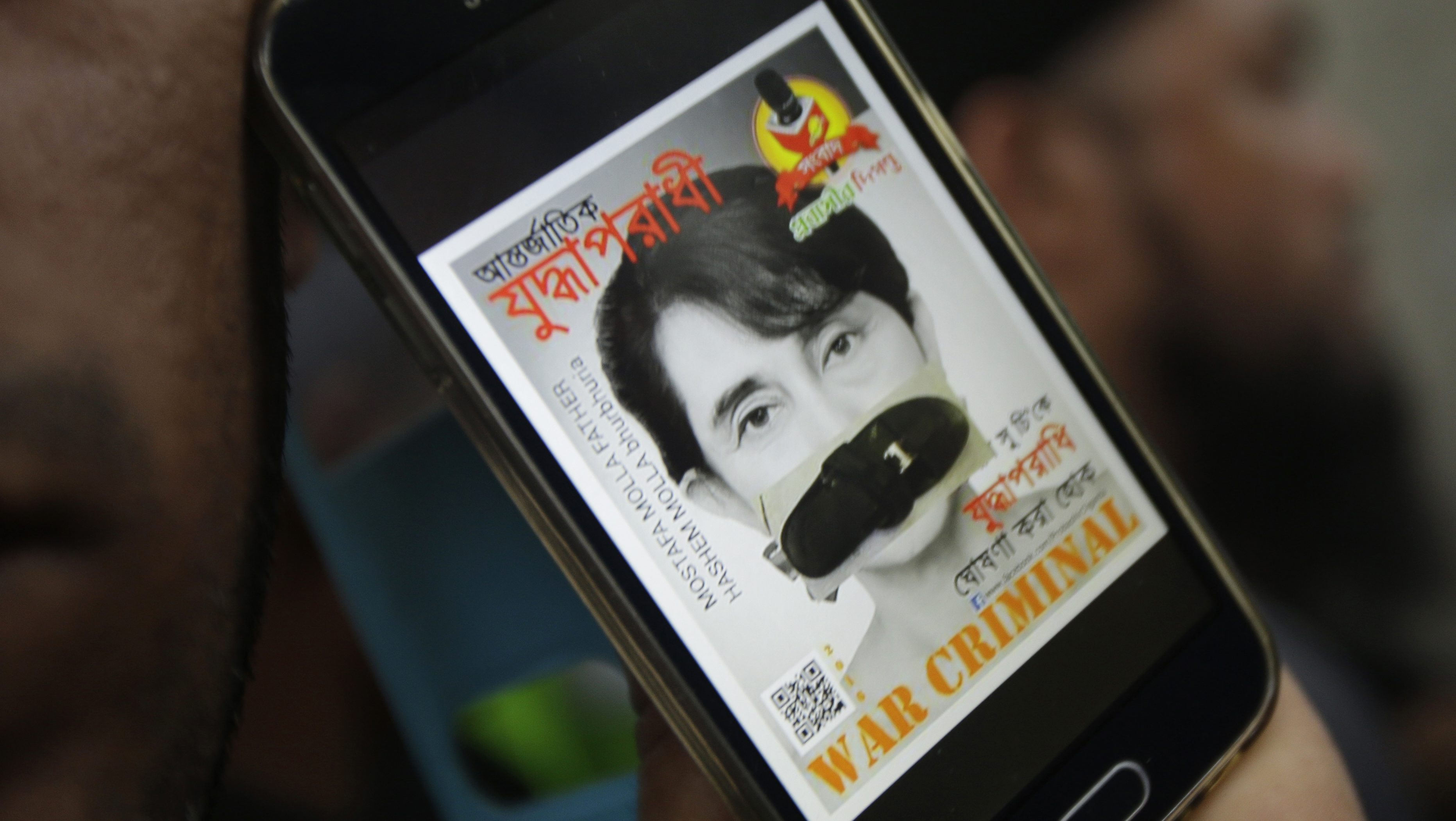 A portrait of Myanmar's Foreign Minister Aung San Suu Kyi with her mouth covered with a sandal displayed on a mobile phone screen is shown by a Rohingya protester during a demonstration in front of the Myanmar Embassy in Bangkok, Thailand, Friday, Nov. 25, 2016 against the persecution of Muslim Rohingya in Myanmar. (AP Photo/Sakchai Lalit)