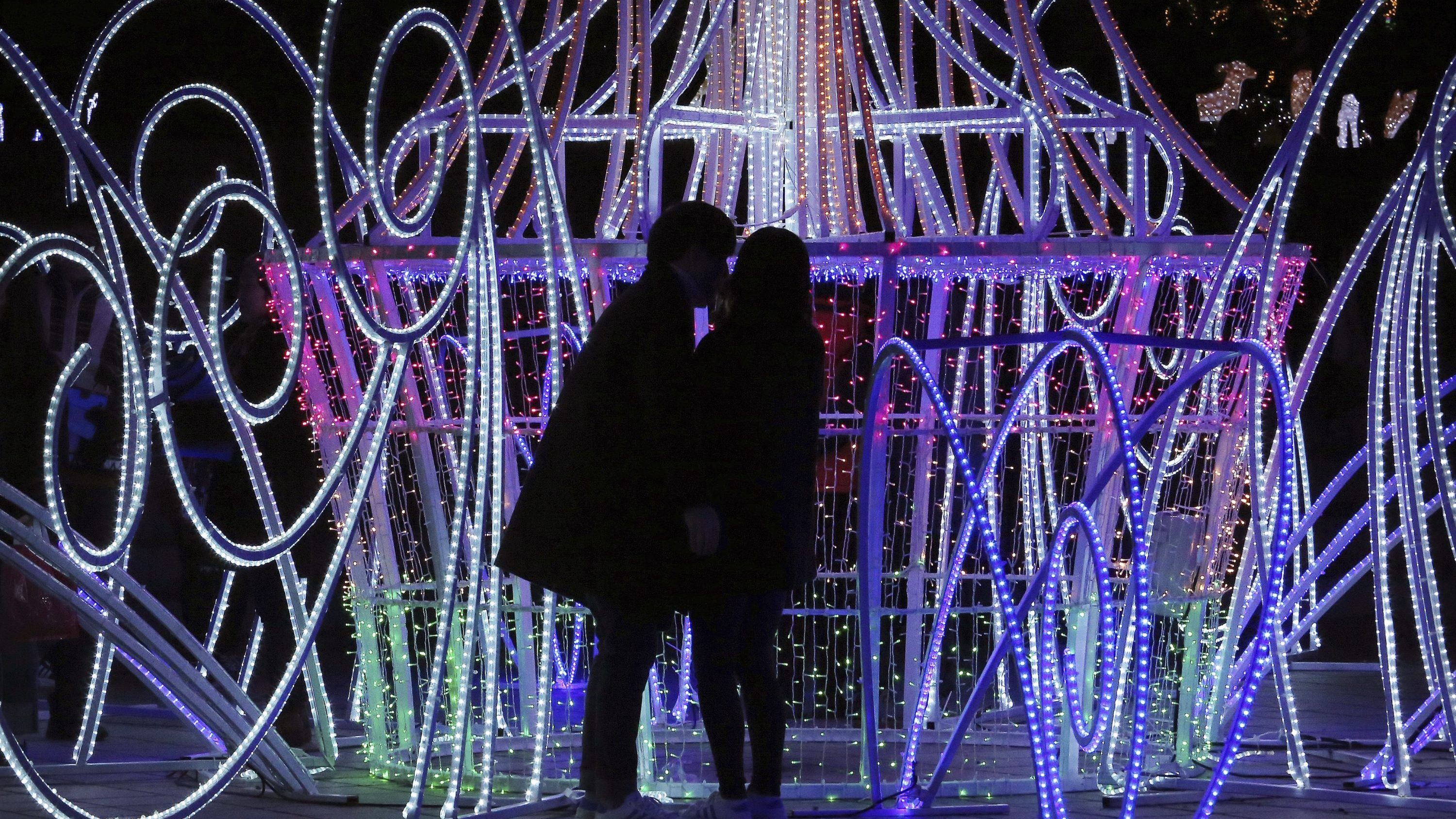A kissing couple is silhouetted against illuminations celebrating the Christmas and New Year holiday season at Ilsan Lake Park in Goyang, South Korea, Sunday, Dec. 25, 2016.