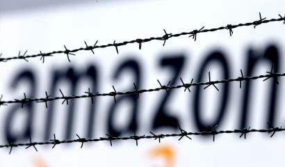 FILE - In this Feb. 19, 2013 file photo, the internet trader Amazon logo is seen behind barbed wire at the company's logistic center in Rheinberg,Germany. The European Union is telling member state Luxembourg to get $295 million in back taxes from Amazon in Brussels' latest regulatory move targeting U.S. tech companies accused of tax avoidance, it was reported on Wednesday, Oct. 4, 2017. (AP Photo/Frank Augstein, File)