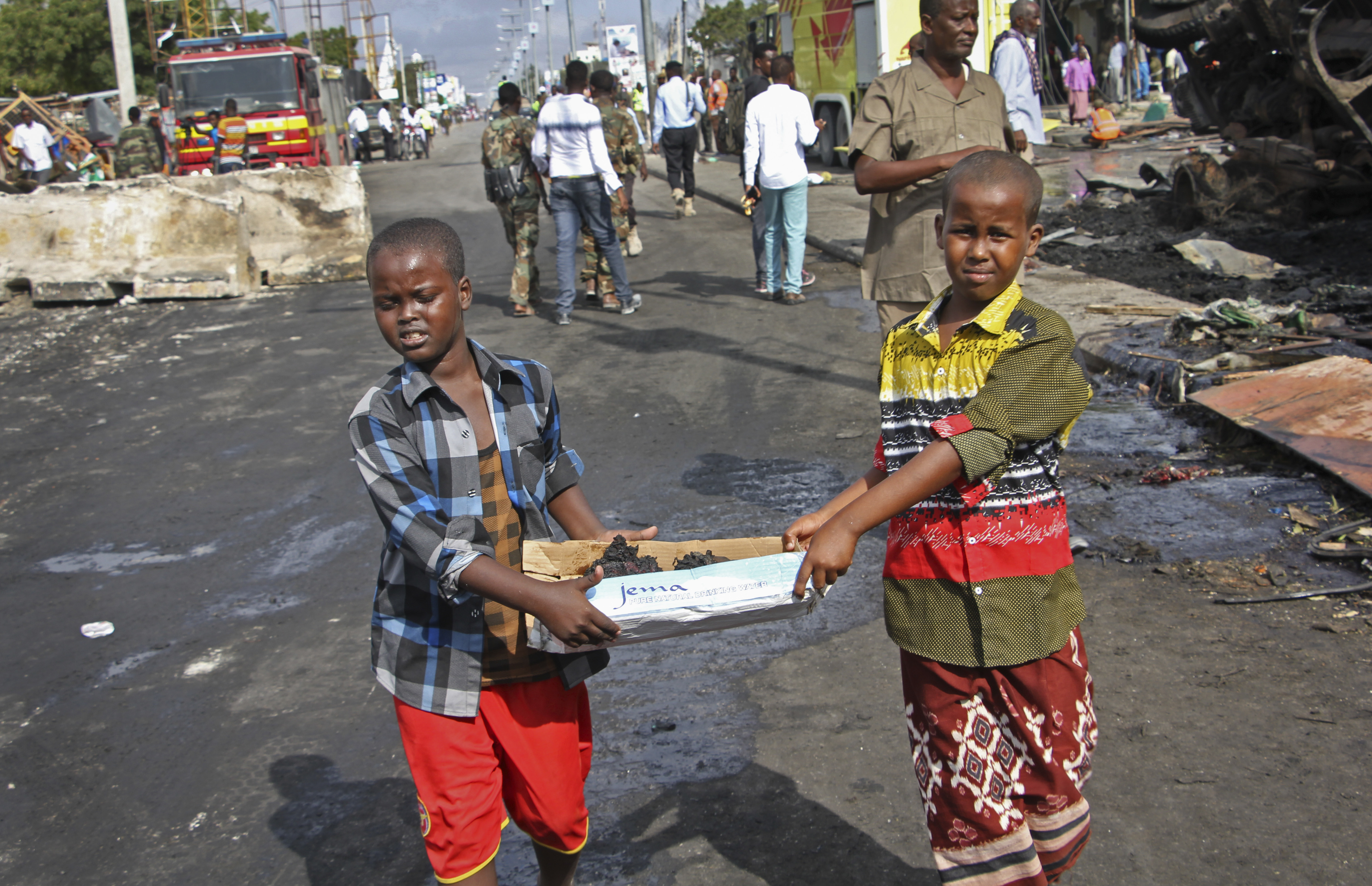 Somali children assist other civilians and security forces in their rescue efforts by carrying away unidentified charred human remains in a cardboard box, to clear the scene of Saturday's blast, in Mogadishu, Somalia, Sunday.