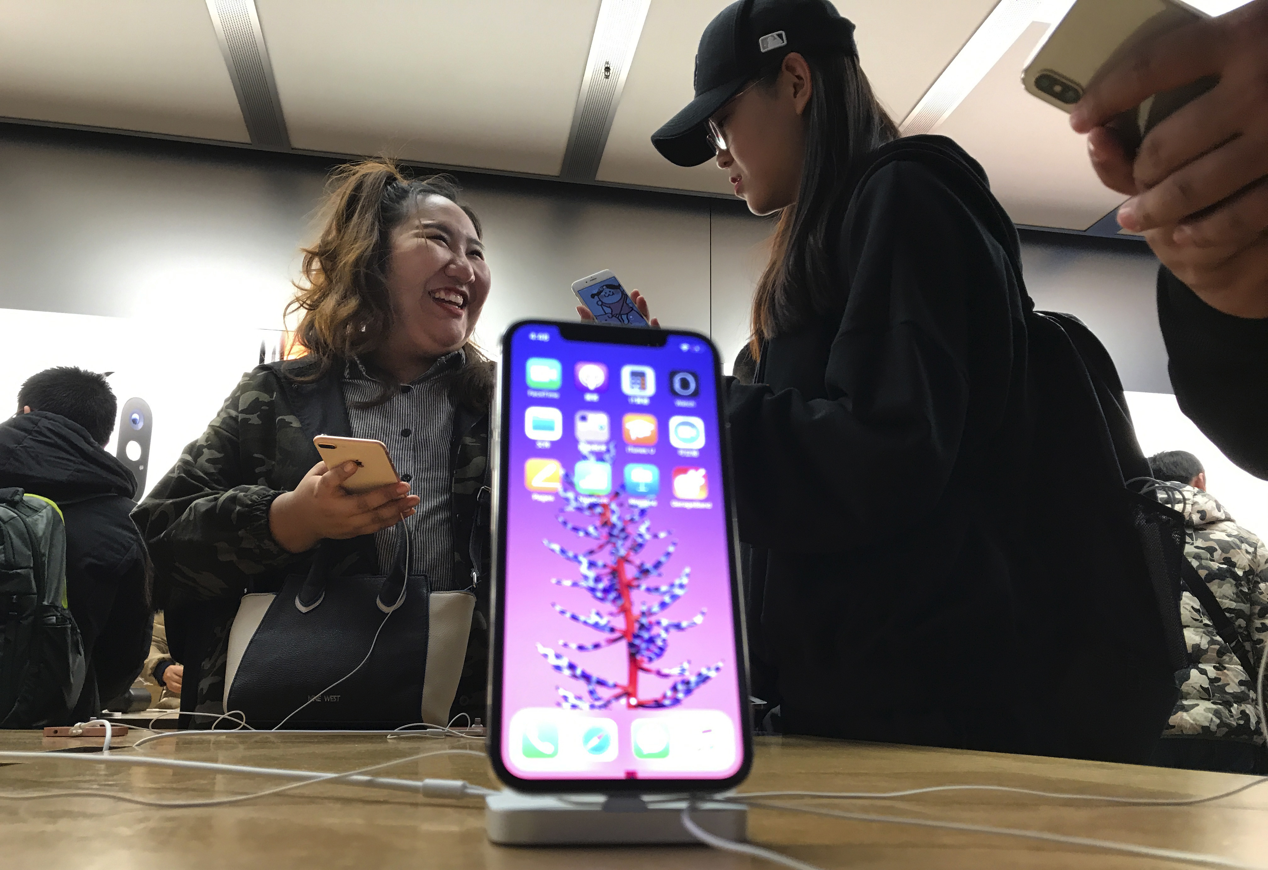 Shoppers check out the iPhone X at an Apple store in Beijing, China, Monday, Nov. 6, 2017. Apple's iPhone X went on sale as the company scrambles to meet demand for a marquee device that sports a lush screen, facial-recognition skills and a $1,000 price tag. (AP Photo/Ng Han Guan)
