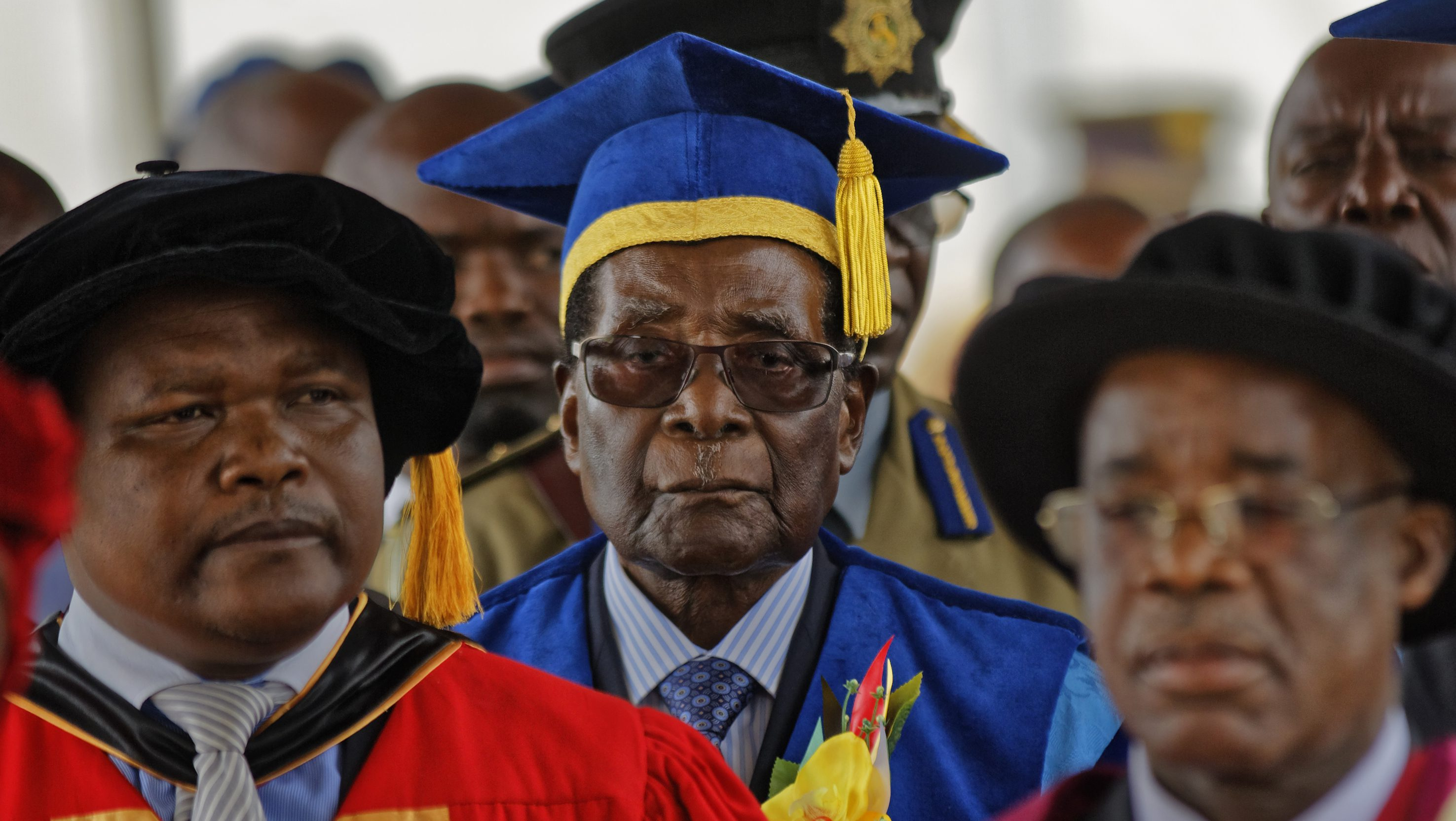 Zimbabwe's President Robert Mugabe, center, arrives to preside over a student graduation ceremony at Zimbabwe Open University on the outskirts of the capital, Harare, on Nov. 17, 2017.