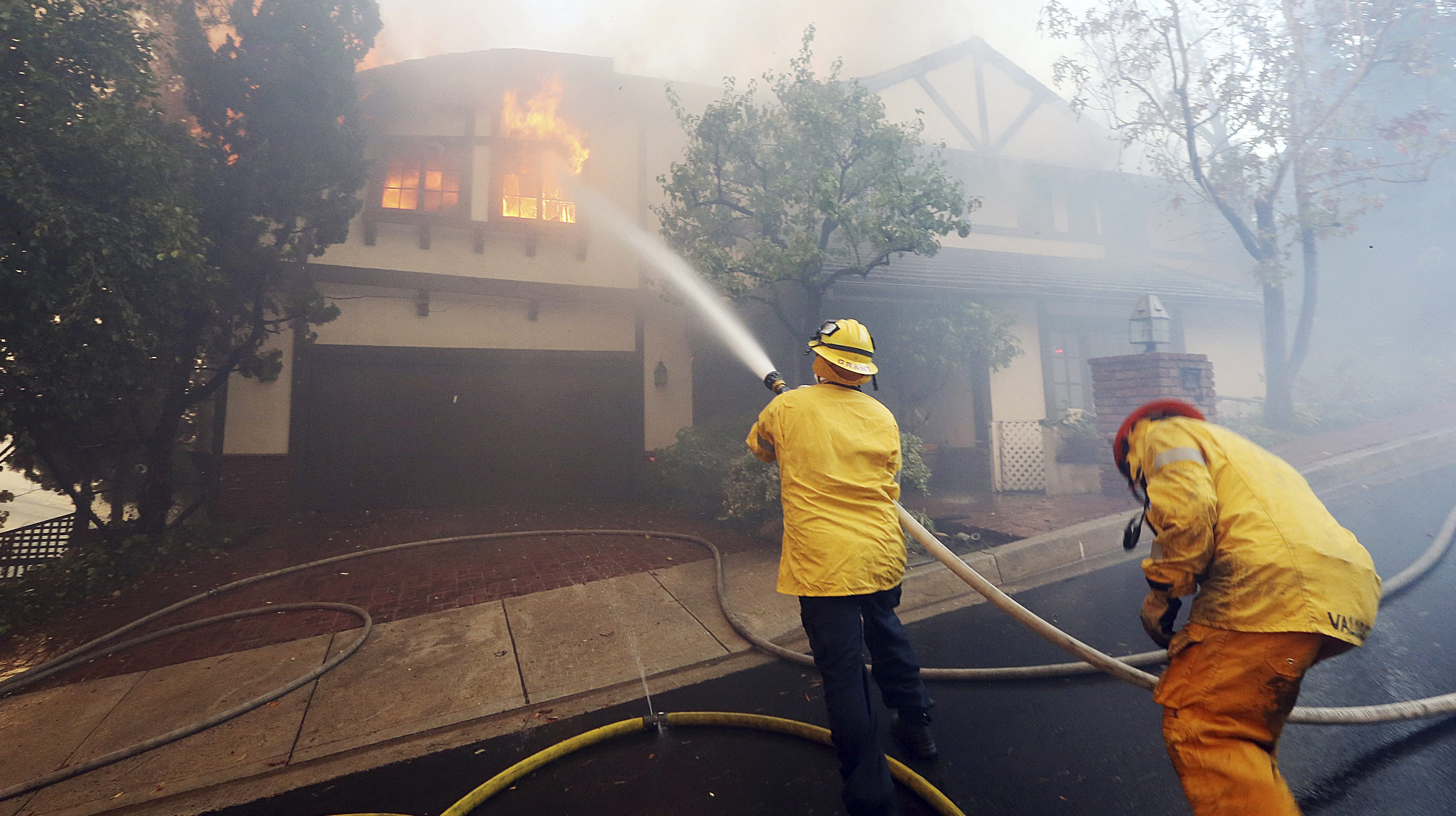 Los Angeles firefighters battle to contain flames to a burning home