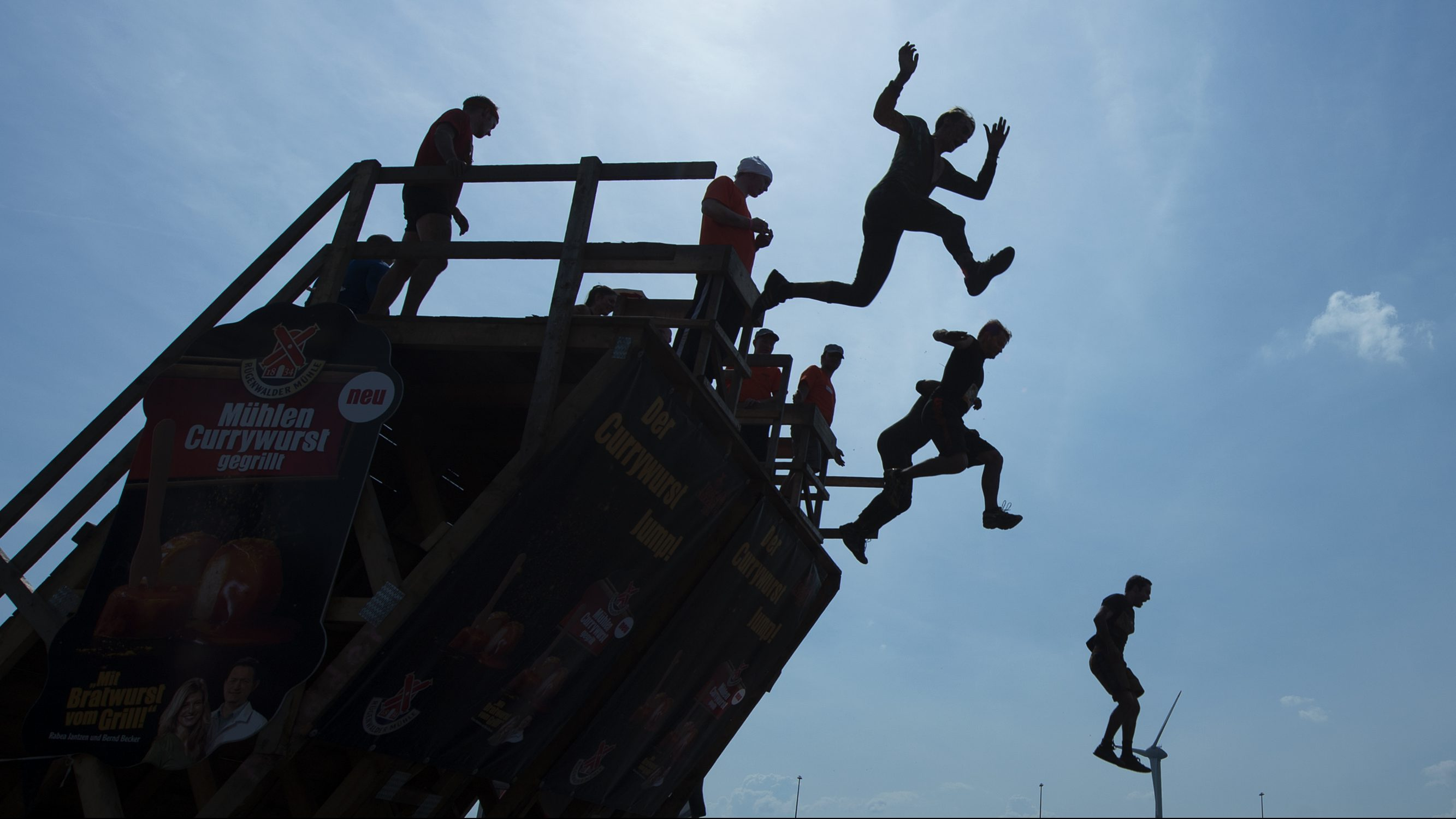 People compete at the Tough Mudder event in Klettwitz, Germany, Saturday, July 26, 2014.  Tough Mudder is a 10-12 miles obstacle course designed to test all-around strength, teamwork, and mental strength.  (AP Photo/Jens Meyer)
