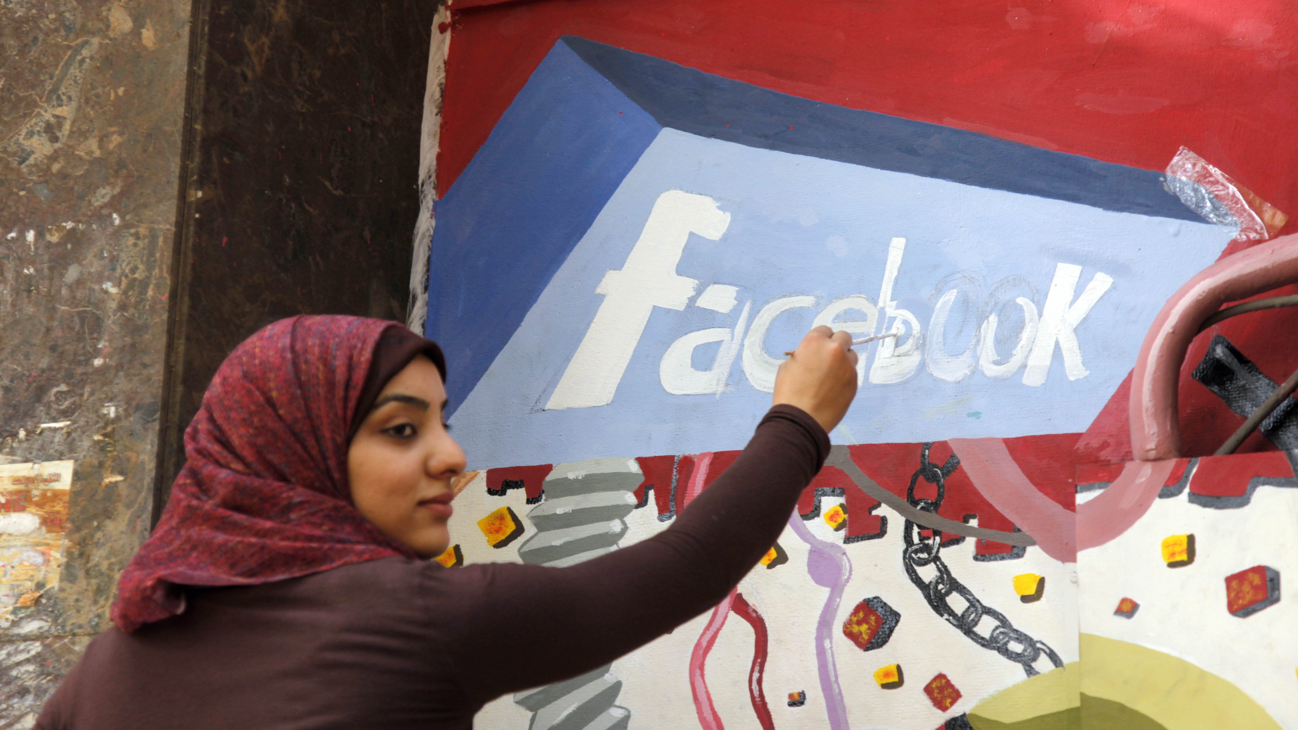 "FILE - In this March 30, 2011, file photo. an art student from the University of Helwan paints the Facebook logo on a mural commemorating the revolution that overthrew Hosni Mubarak in the Zamalek neighborhood of Cairo, Egypt. In a statement to The Associated Press on Wednesday, Dec 30, 2015, Facebook said it is ""disappointed"" that a program providing free basic Internet services to over three million Egyptians has been shut down. It said the service provided Internet access to more than a million people who were not previously connected."