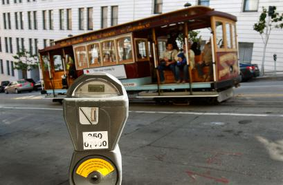 In this Oct. 27, 2009 file photo, a cable car passes a parking meter near San Francisco's financial district. San Francisco City Attorney Dennis Herrera on Monday, June 23, 2014 issued a cease-and-desist demand to a mobile app called Monkey Parking, which allows people to auction off public parking spaces that they're using to other nearby drivers.