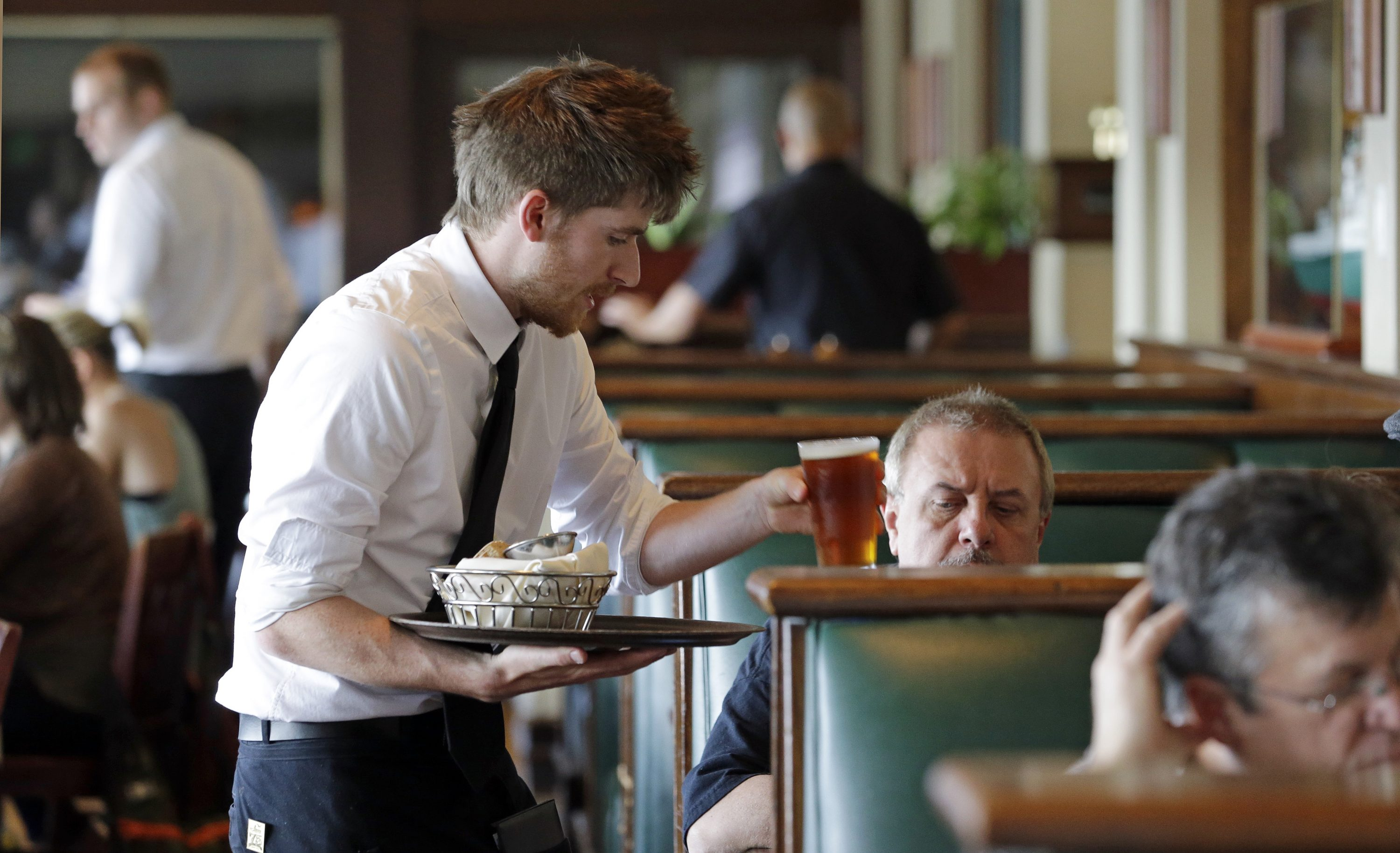 FILE - In this May 14, 2014, file photo, waiter Spencer Meline serves a customer at Ivar's Acres of Clams restaurant on the Seattle waterfront. The Institute for Supply Management, a trade group of purchasing managers, issues its index of non-manufacturing activity for May 2015, on Wednesday, June 3, 2015.
