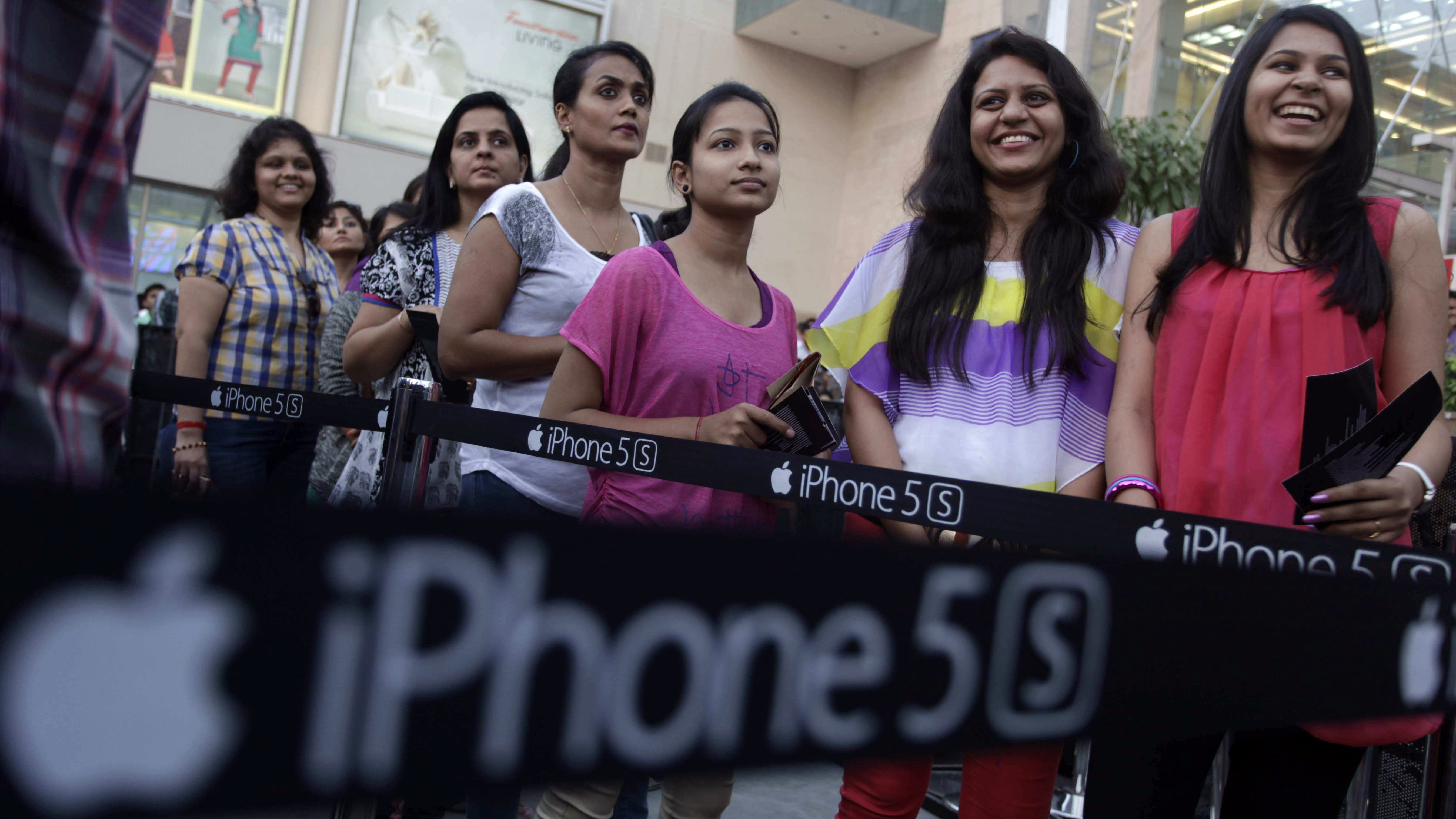 Indians stand in a queue to purchase the newly launched iPhone 5c and 5s in Ahmadabad, India, Friday, Nov. 1, 2013. Apple's newest iPhones, the iPhone 5s and the cheaper iPhone 5c, are now officially available in the Indian markets starting Friday. (AP Photo/Ajit Solanki)