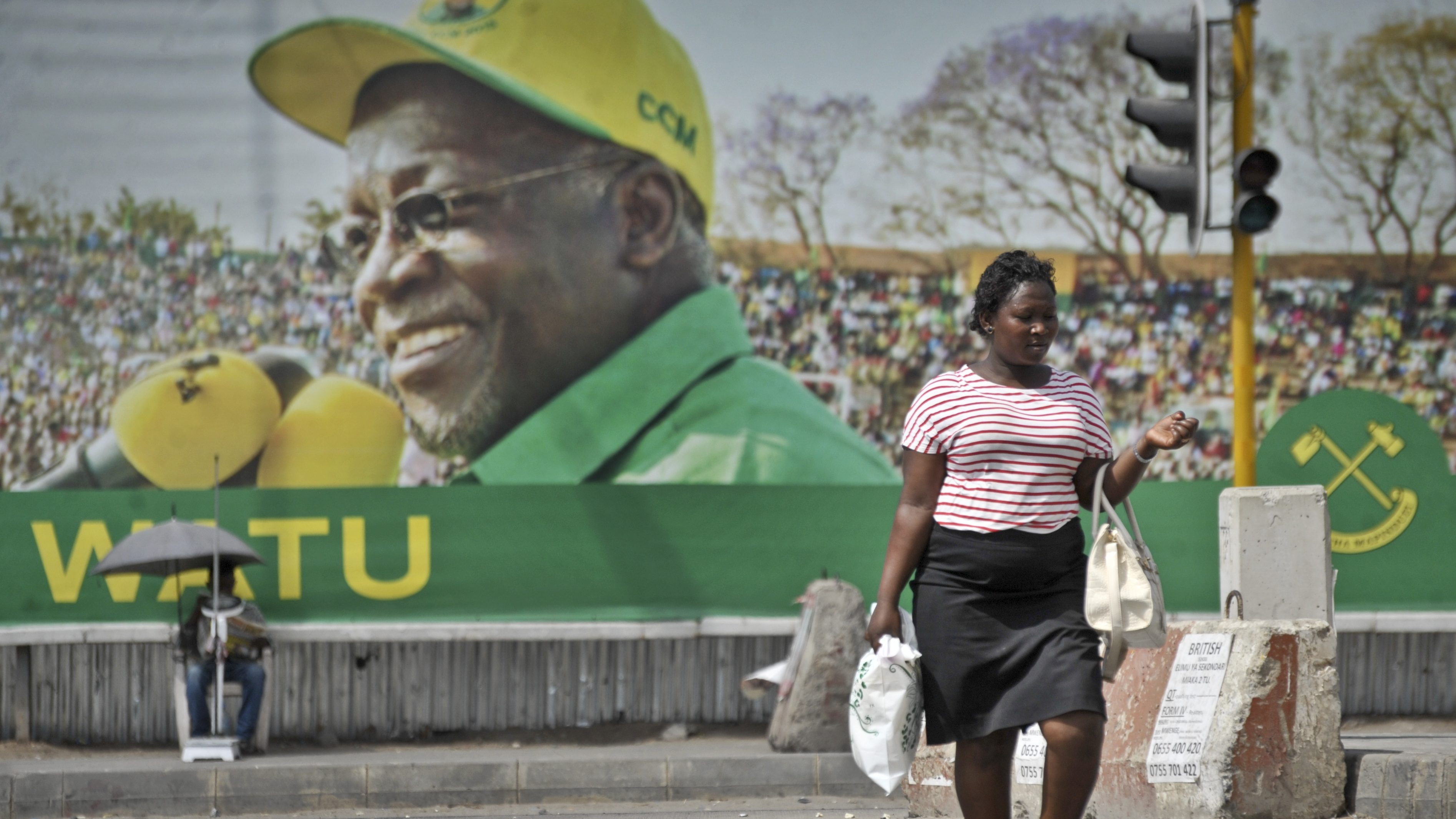 A Tanzanian woman walks past a billboard for the ruling party's presidential candidate John Magufuli, in Dar es Salaam, Tanzania Monday, Oct. 26, 2015. Tanzanians turned out in large numbers Sunday to vote in general elections in which the ruling party, in power for decades, faces a strong challenge from a united opposition, with the ruling party's candidate John Magufuli battling former Prime Minister Edward Lowassa, in a presidential race many analysts say is too close to predict.