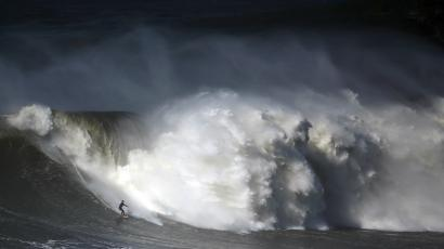 A surfer drops in on a large wave