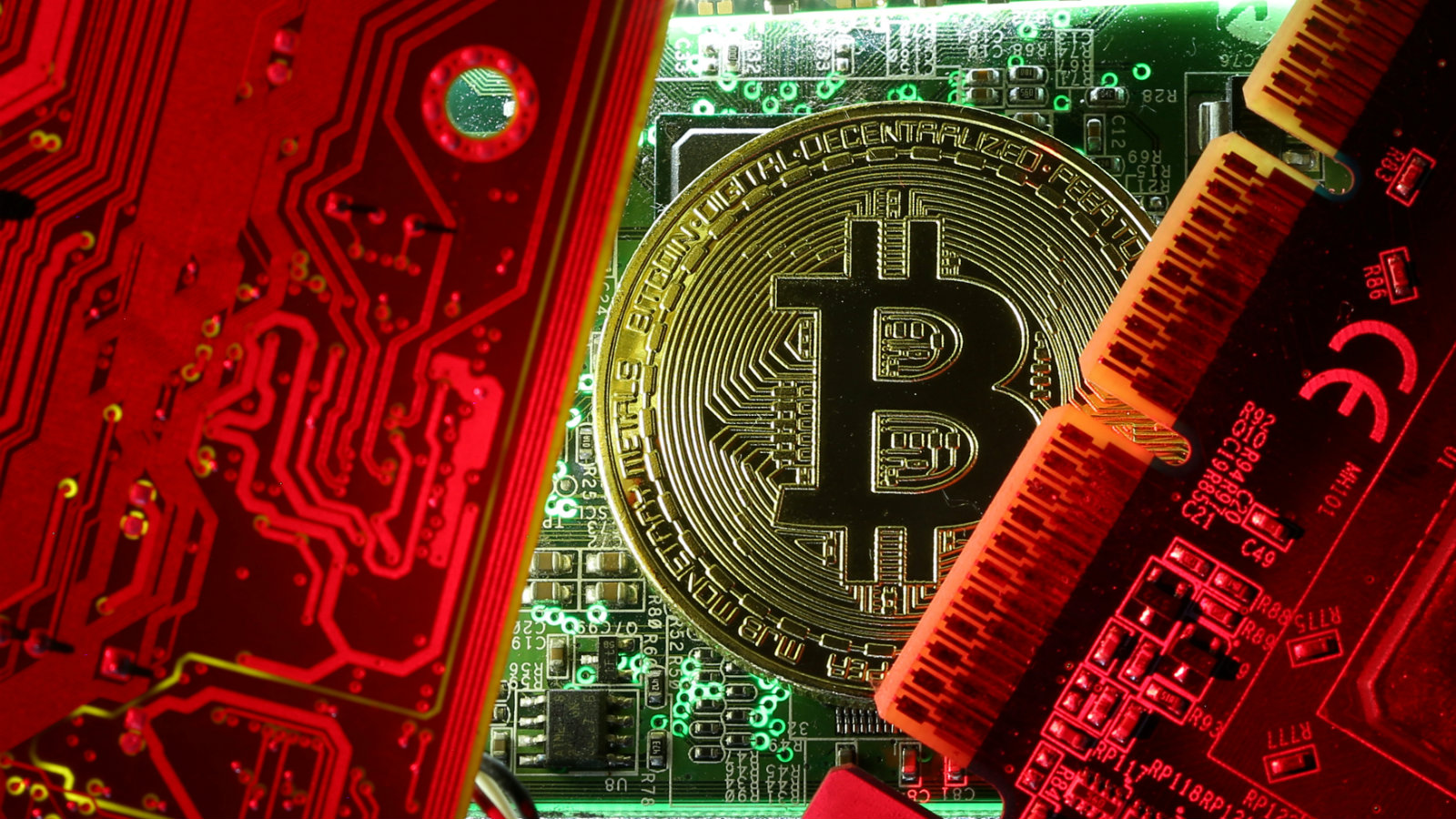 A coin representing the bitcoin cryptocurrency is seen on computer circuit boards in this
