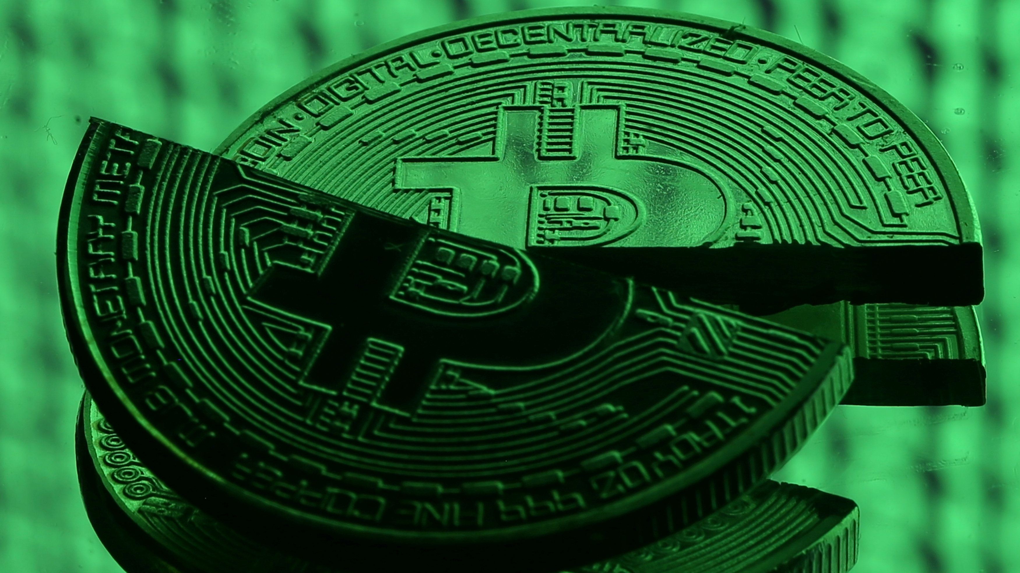 Broken representations of the Bitcoin virtual currency, placed on a monitor that displays binary digits, are seen in this illustration picture, December 8, 2017. REUTERS/Dado Ruvic
