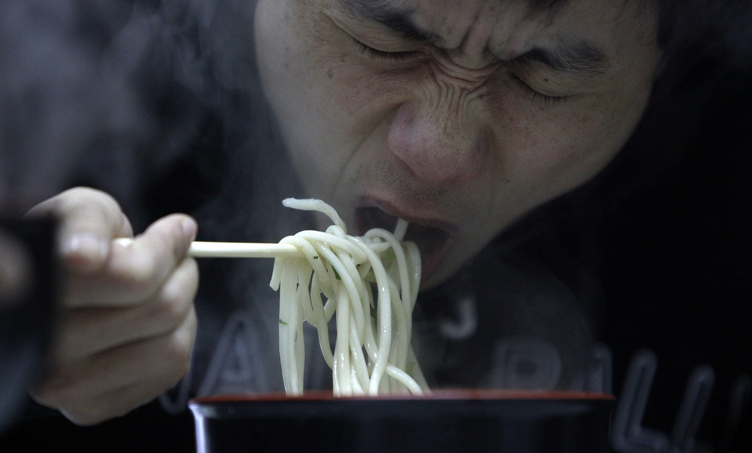 """A man eats noodle at a restaurant in Shanghai March 2, 2009. China said on Monday food security remains """"grim"""", despite campaigns launched after several health scares, the most recent last year's tainted milk formula which killed at least six toddlers and made almost 300,000 sick."""