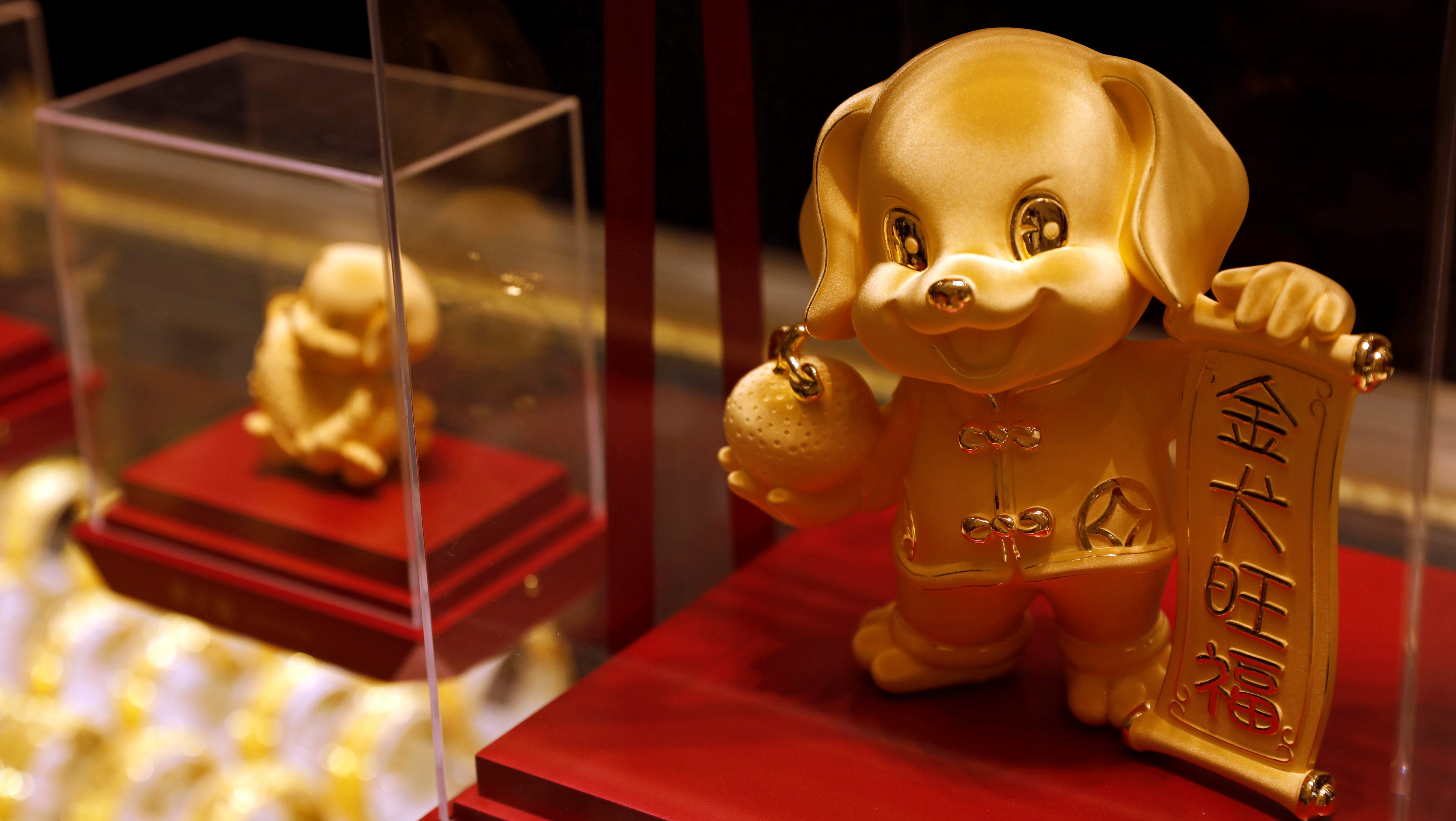 Dog-shaped gold figurines are displayed at Chow Tai Fook Jewellery store ahead of the Lunar Year of the Dog in Hong Kong, China December 14, 2017. REUTERS/Tyrone Siu - RC1E7722AEF0