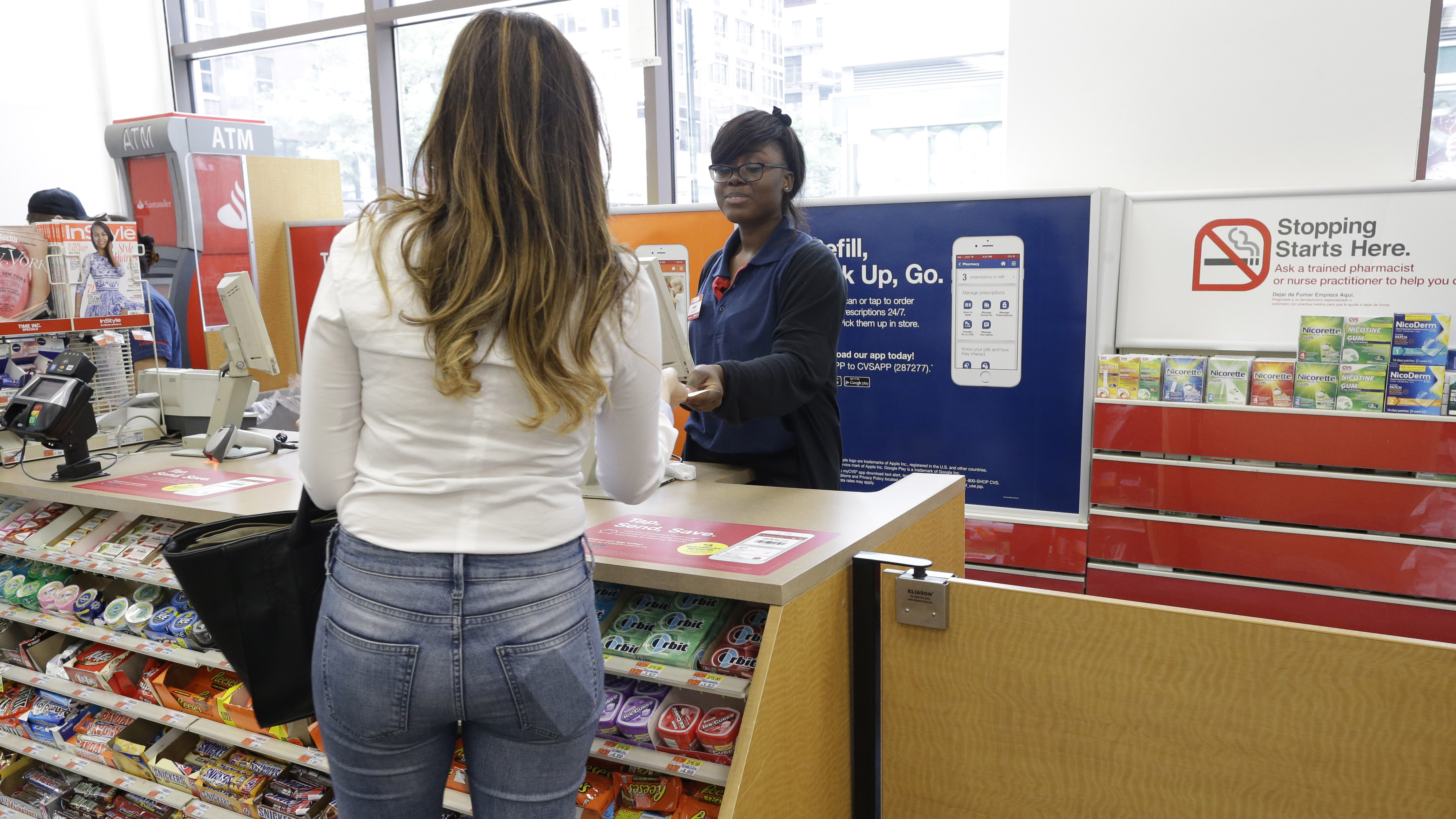 A cashier helps a customer as smoking cessation products are on display where cigarettes used to be at the front of the CVS drugstore in Midtown Manhattan, Wednesday, June 17, 2015. CVS drugstores that quit tobacco sales last year are now getting health and beauty makeovers to attract customers who want more than a prescription refill. (AP Photo/Mary Altaffer)