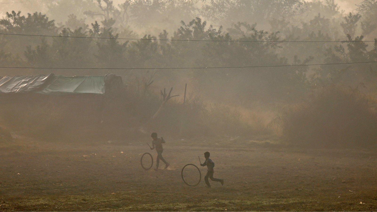 Boys play with rubber tyres on the banks of the Yamuna river on a smoggy morning in New Delhi, India, November 30, 2017.