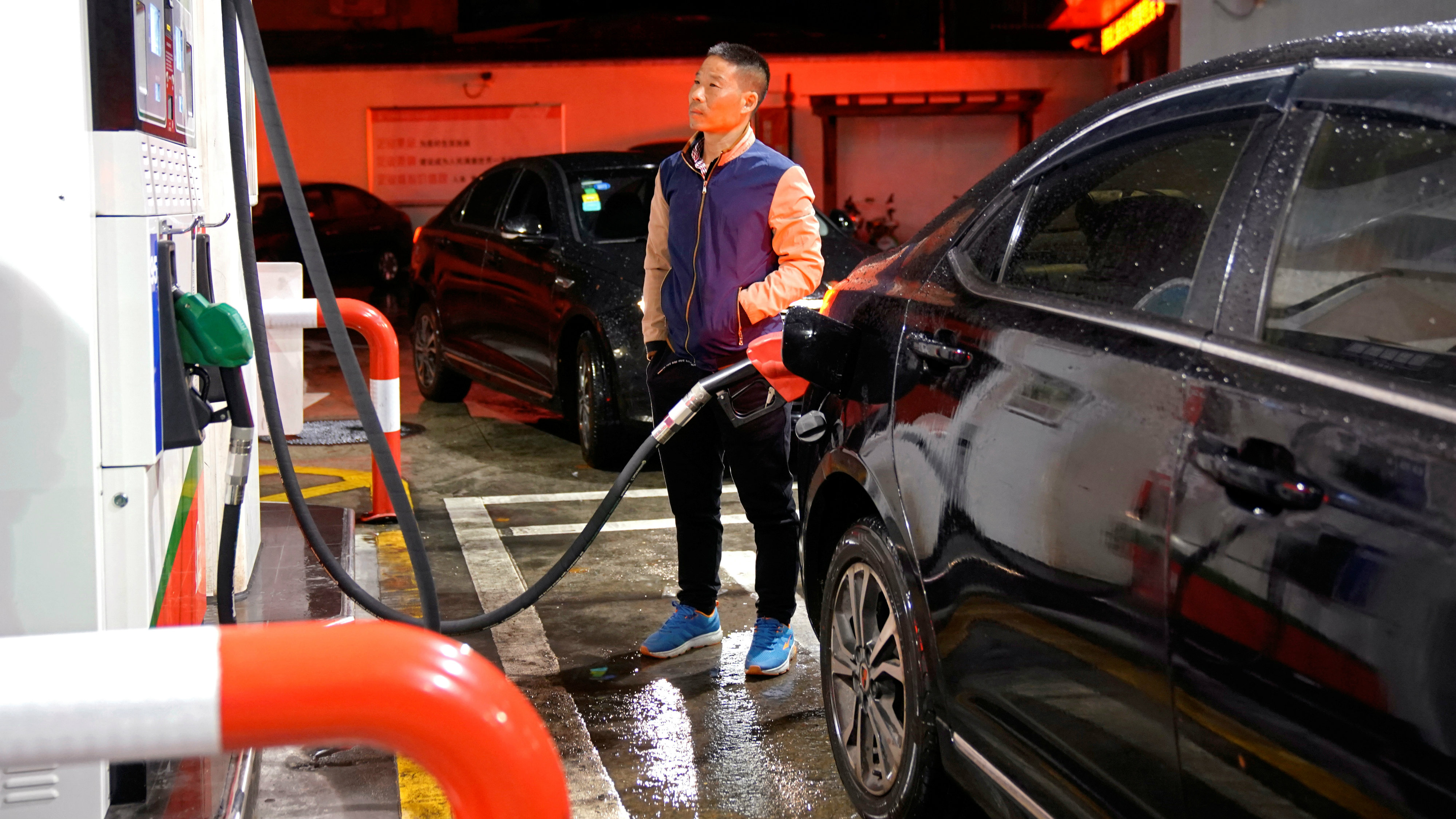 A driver looks at the price as he fills the tank of his car at a gas station in Shanghai, China November 17, 2017