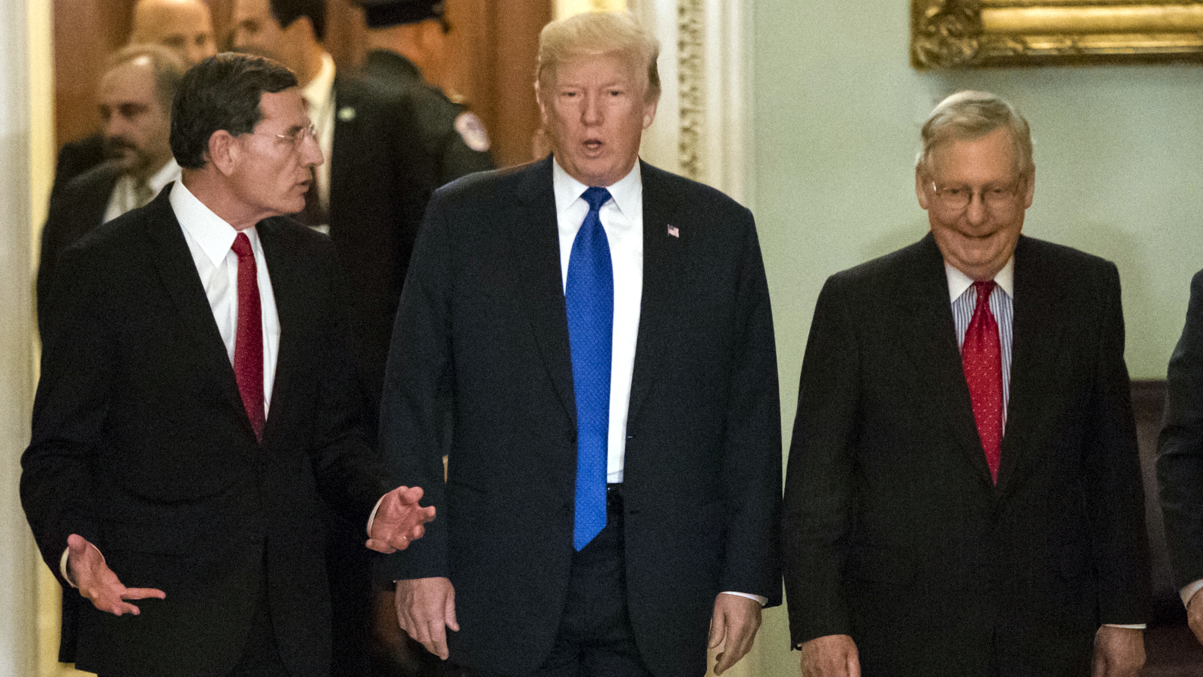 President Donald Trump, center, escorted by Sen. John Barrasso, R-Wyo., chairman of the Senate Republican Policy Committee, left, and Senate Majority Leader Mitch McConnell, R-Ky., right, arrives at the Capitol to meet with GOP lawmakers about moving his agenda and passing the Republican tax bill, in Washington, Tuesday, Nov. 28, 2017.