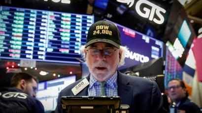 Trader on NYSE floor in a Dow 24K hat