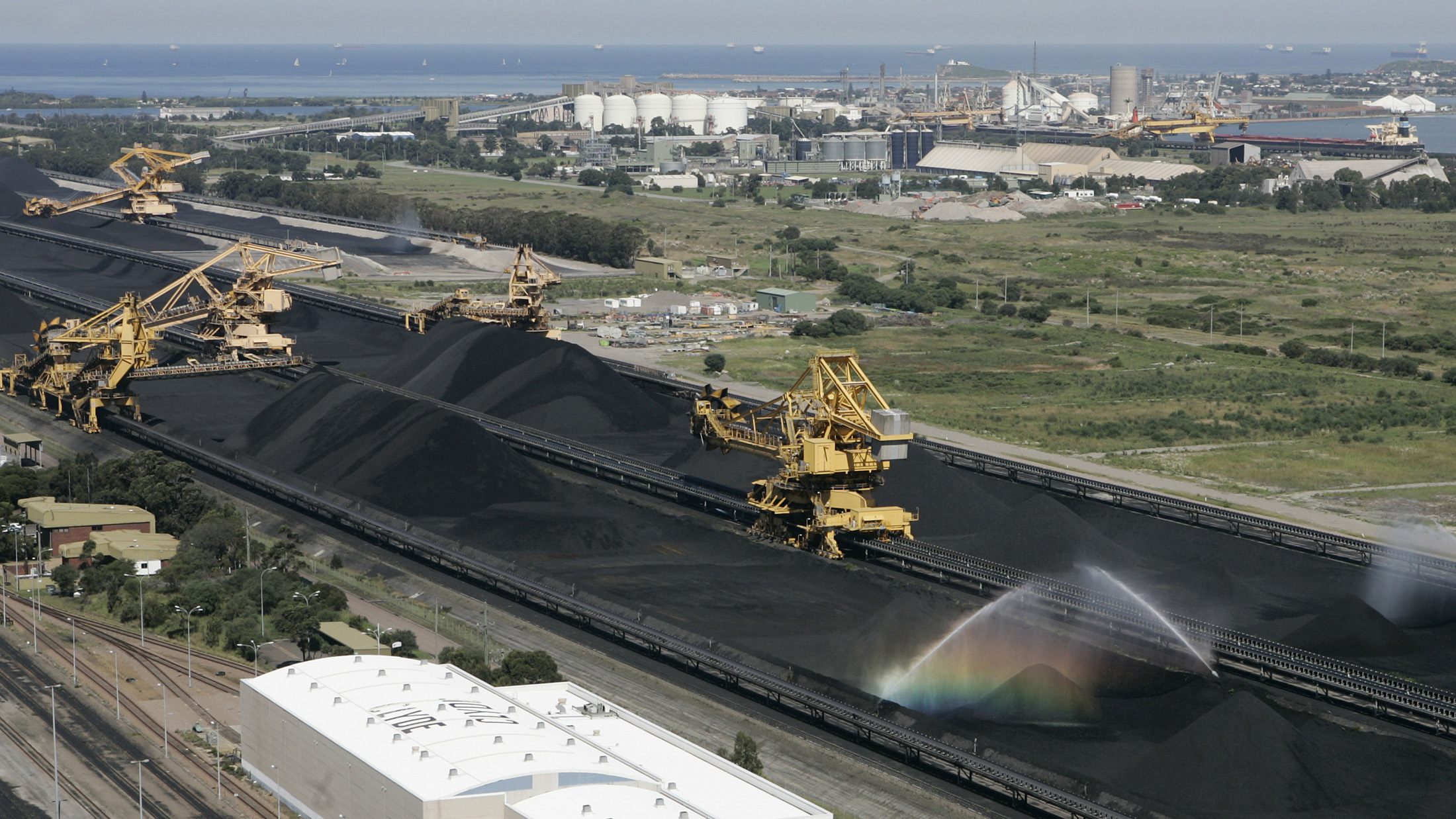 Coal is kept moist as it sits in piles waiting to be loaded onto container ships at the world's biggest coal export terminal in Newcastle, located 120 km (75 miles) north of Sydney March 11, 2007. Australian coal exports from Newcastle port rebounded about 40 percent in the past week, from a five-month low, as the port's facilities resumed following a disruption last week due to planned maintenance. Picture taken March 11, 2007. REUTERS/David Gray (AUSTRALIA) - GM1DVAAXAVAA