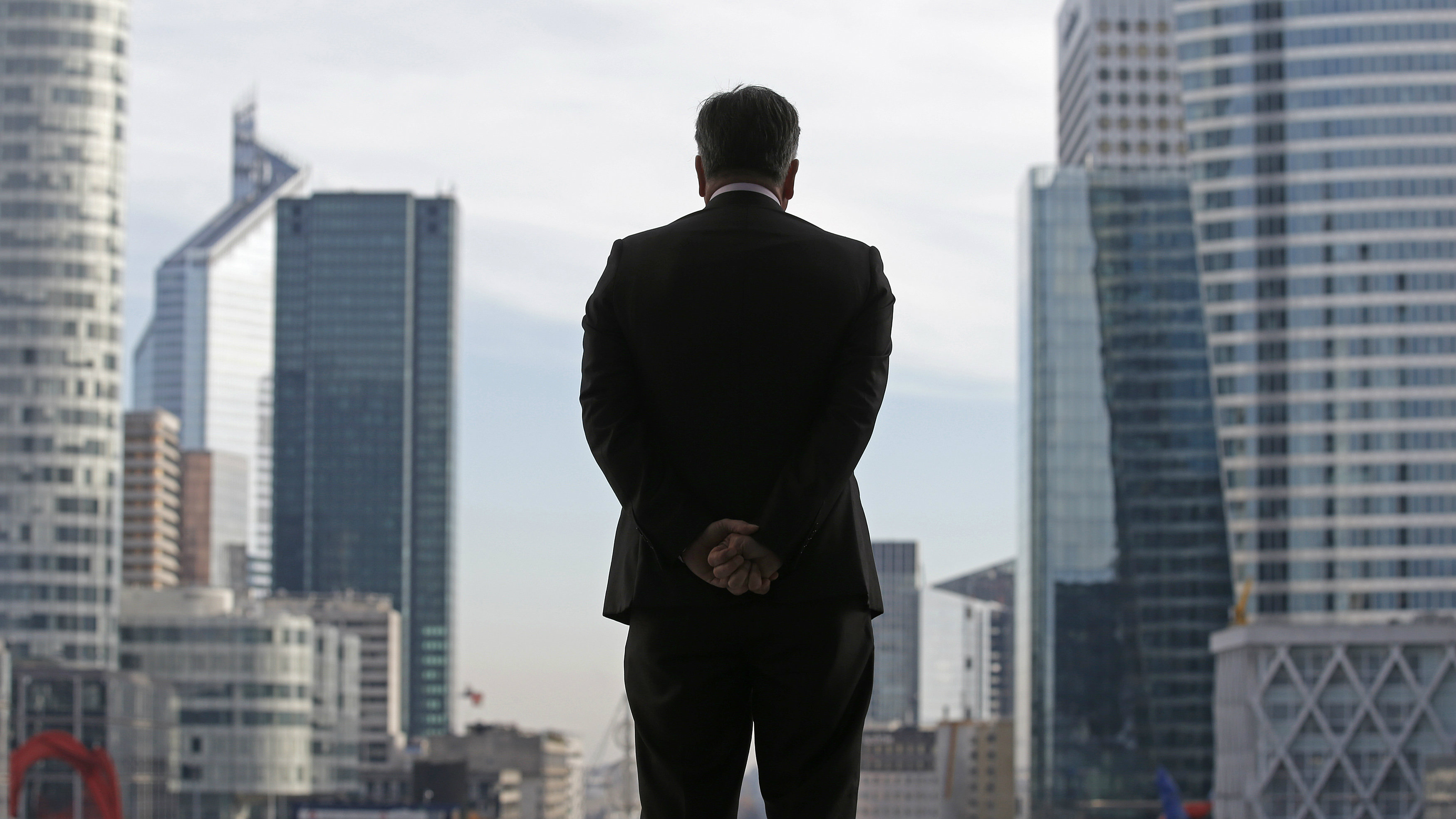 A Businessman is silhouetted as he stands under the Arche de la Defense, in the financial district west of Paris, November 20, 2012. France said its economy was sound and reforms were on track after credit ratings agency Moody's stripped it of the prized triple-A badge due to an uncertain fiscal and economic outlook. Monday's downgrade, which follows a cut by Standard & Poor's in January, was expected but is a blow to Socialist President Francois Hollande as he tries to fix France's finances and revive the euro zone's second largest economy.
