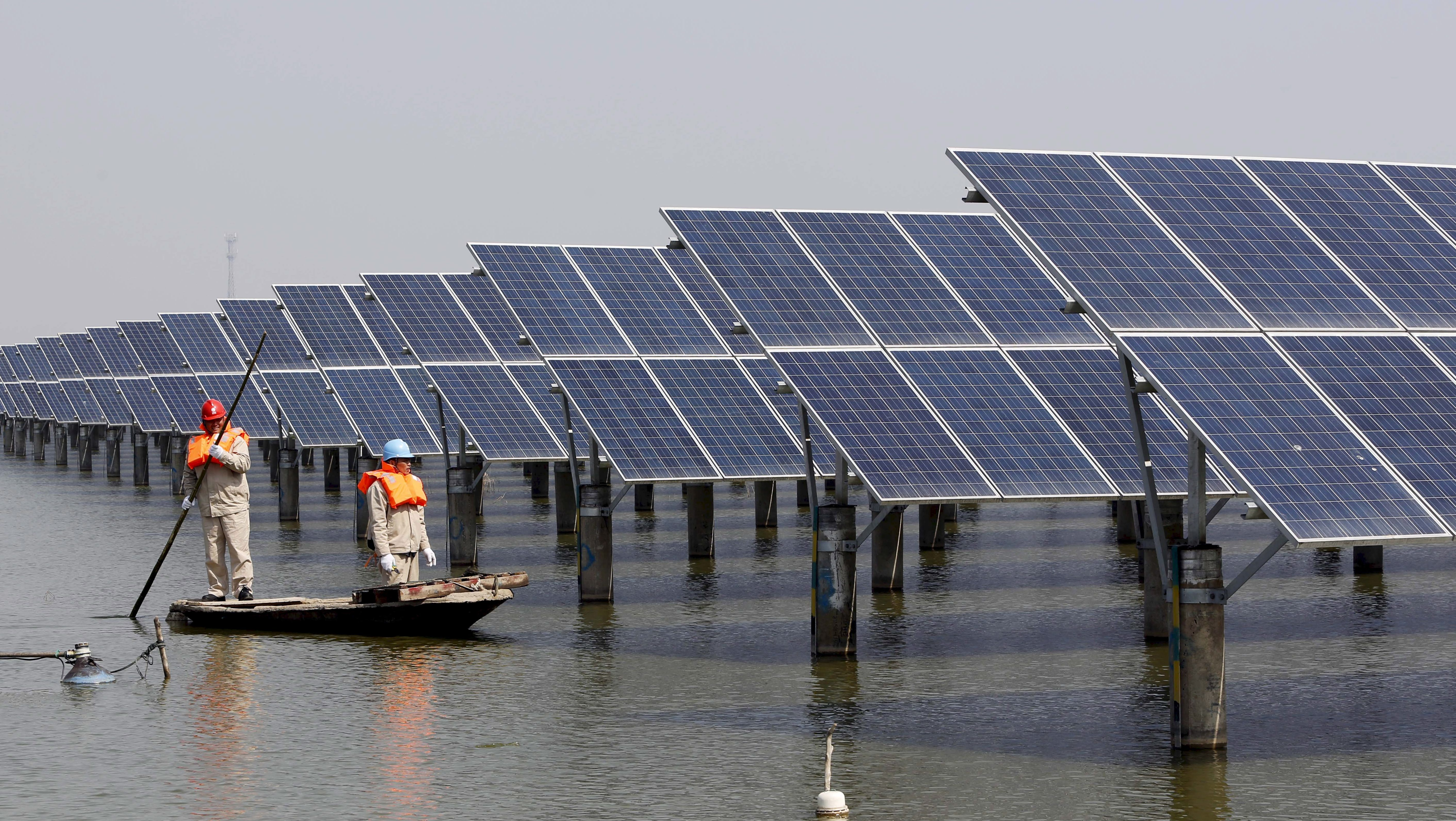 Employees row a boat as they examine solar panel boards at a pond in Lianyungang, Jiangsu Province, China, in this March 16, 2016 file photo. Global funds are cautiously venturing back into Chinese equities after prices collapsed to 4-1/2-year lows in February, taking advantage of cheaper valuations to buy stocks they believe will benefit from China's shift to a consumption-led economy.