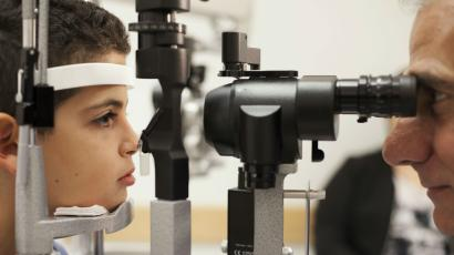 An eye doctor looking into a child's eyes.