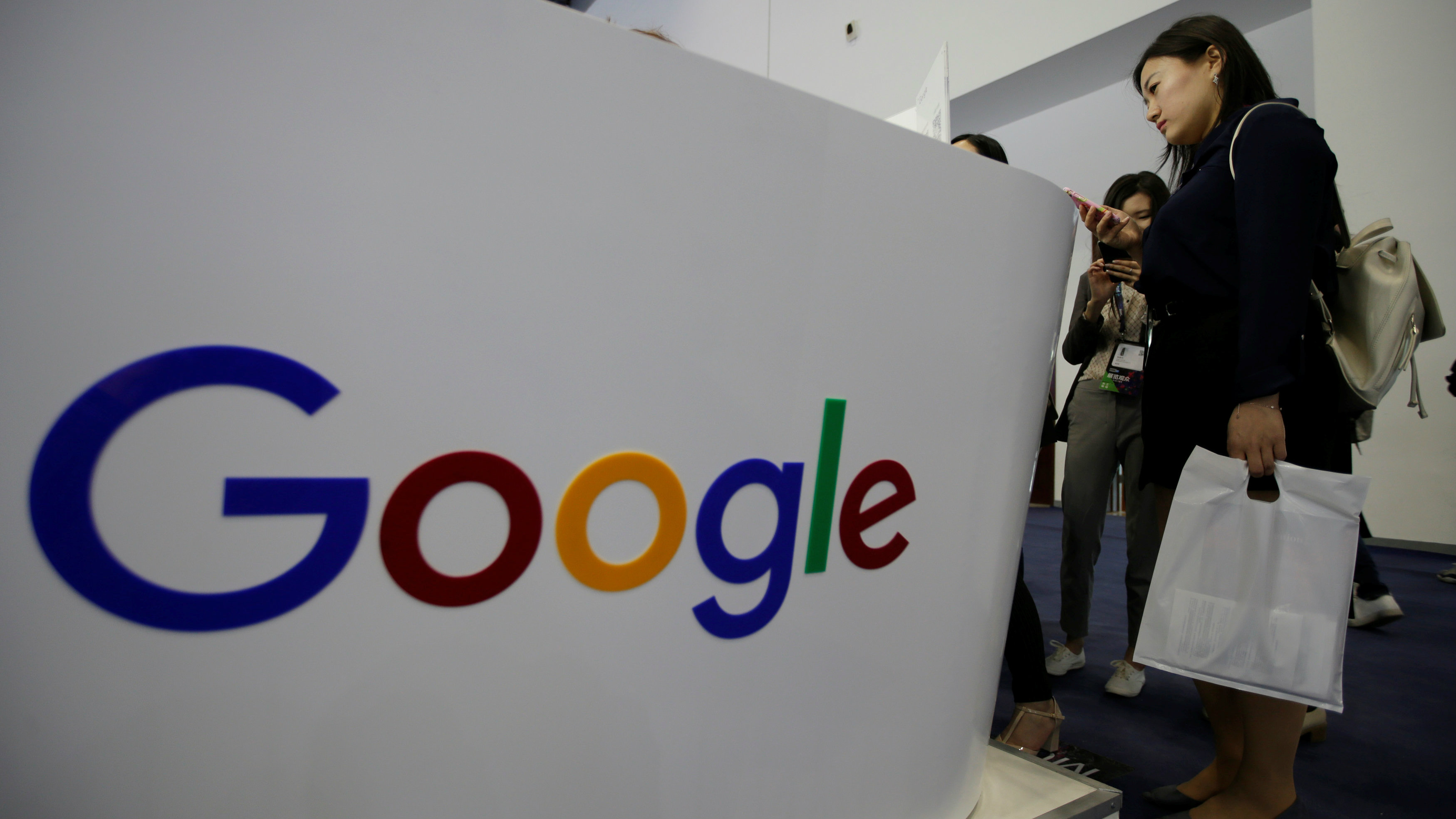 People visit Google's booth at the Global Mobile Internet Conference (GMIC) 2017 in Beijing