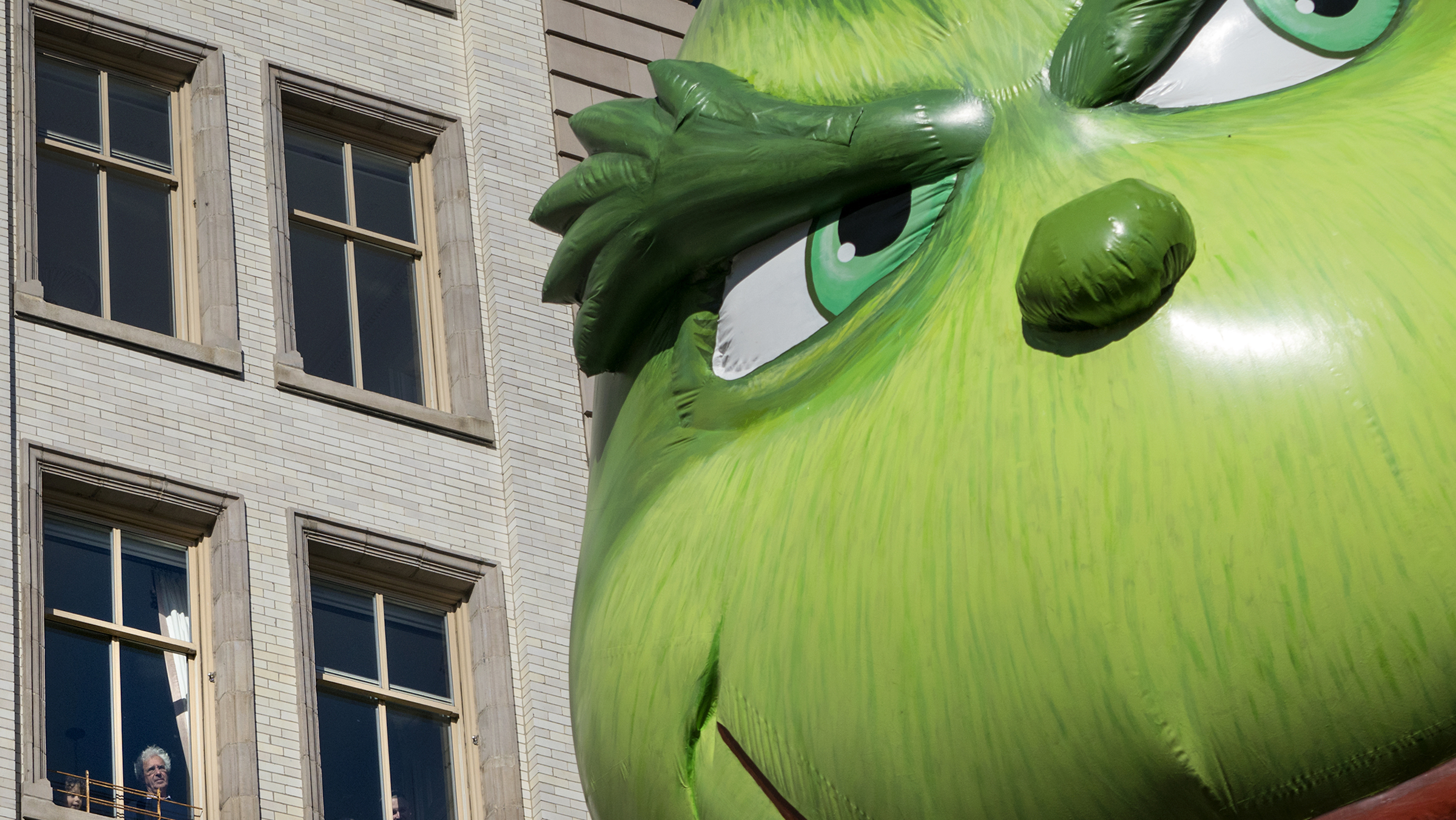 The Grinch balloon passes by windows of a building on Central Park West during Macy's Thanksgiving Day Parade in New York Thursday, Nov. 23, 2017.
