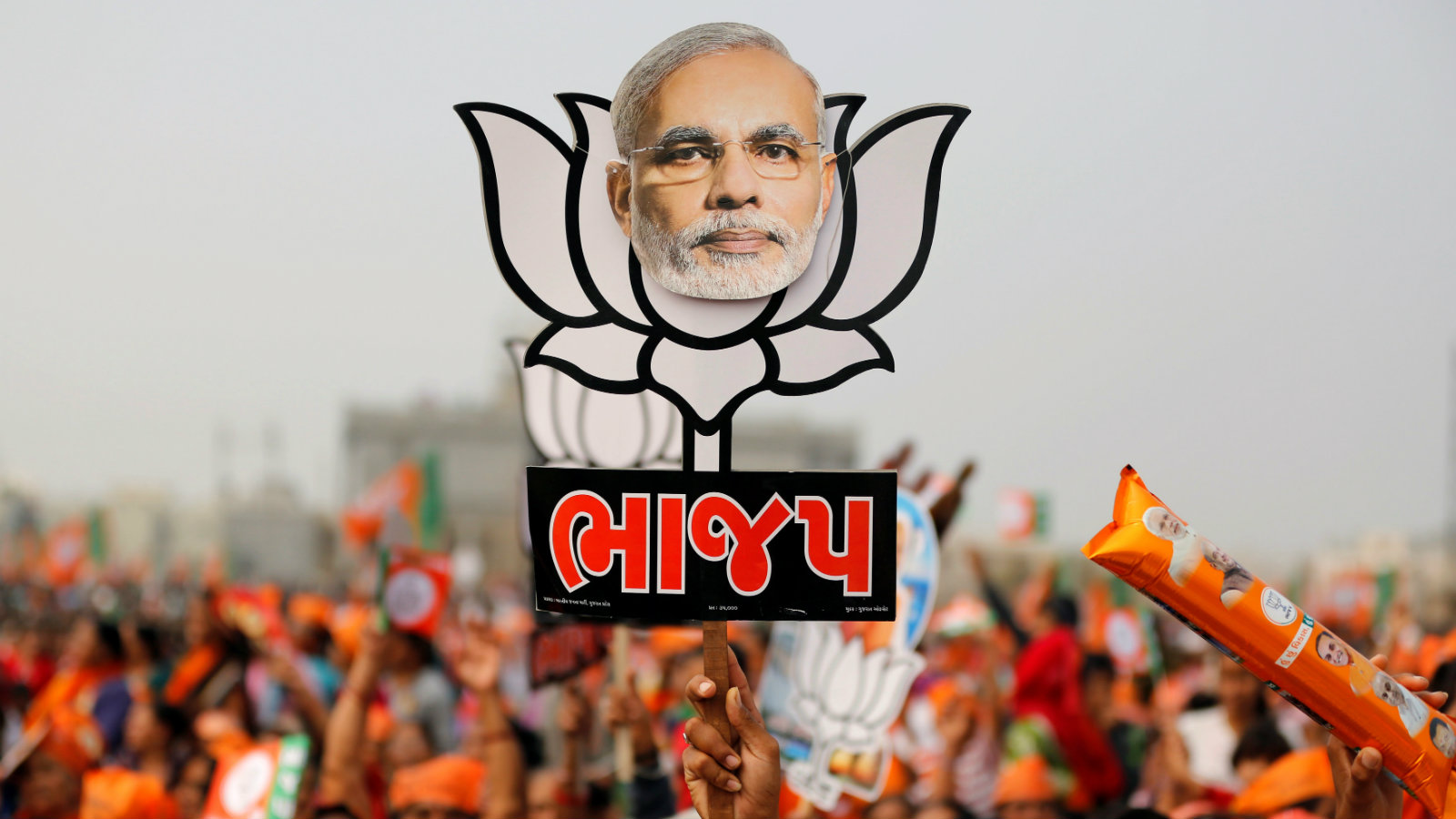 A supporter holds up a cut-out of a lotus, the election symbol of India's ruling Bharatiya Janata party (BJP), with an image of Prime Minister Narendra Modi during a campaign meeting addressed by Modi ahead of Gujarat state assembly election in Kalol on the outskirts of Ahmedabad, India, December 8, 2017.