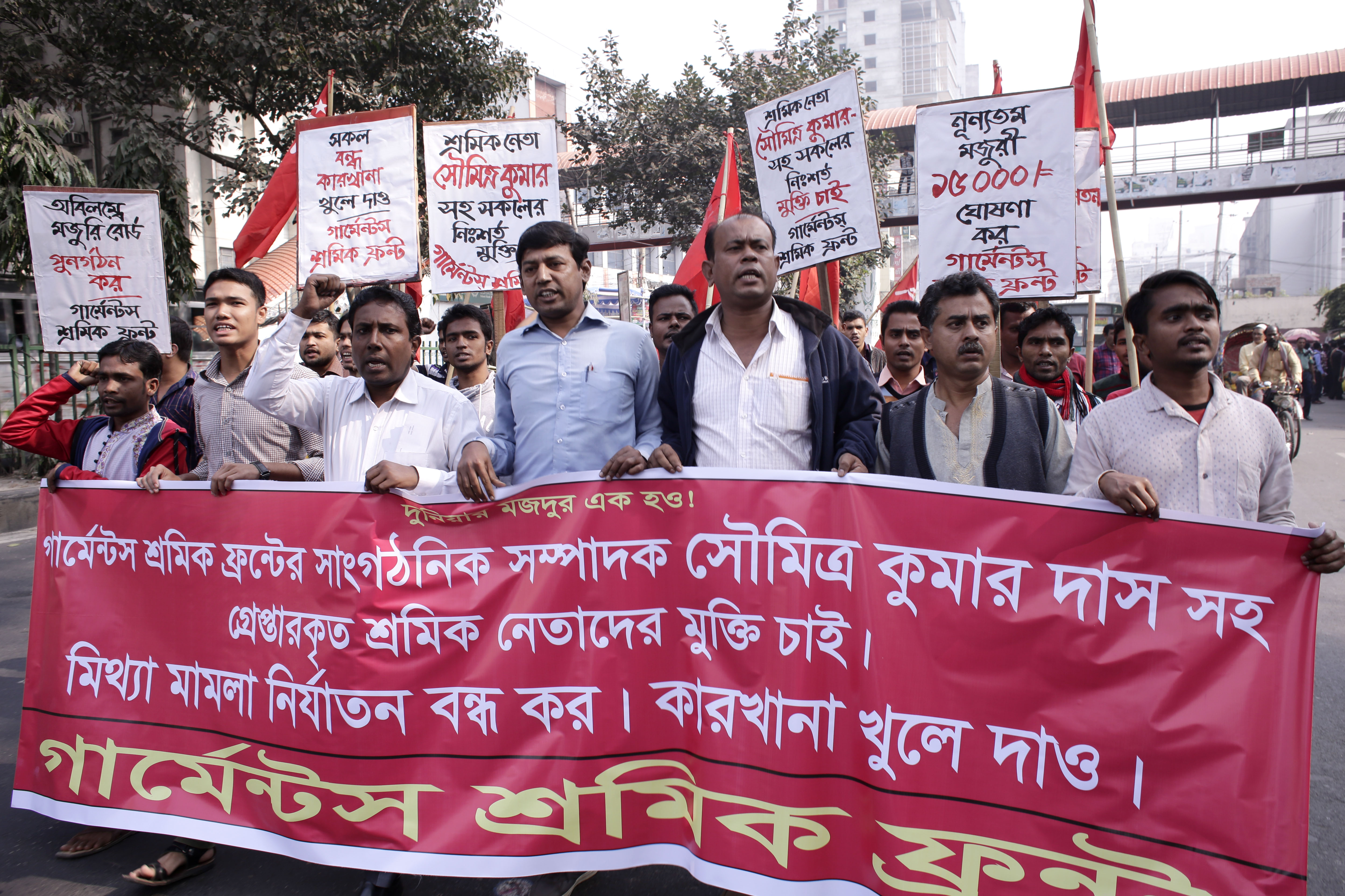 epa05686314 Workers and leaders of the Garments Sromik Front attend a rally protesting the arrests of their leaders and termination of workers from several factories following unrest in Dhaka, Bangladesh, 23 December 2016. At least 278 workers of two readymade garment factories were terminated for instigating labor unrest at Ashulia industrial belt on 21 and 22 December 2016, while the workers have been demonstrating and demanding increase of minimum wage to Euro 200 from Euro 66.25 since 11 December 2016. EPA/ABIR ABDULLAH