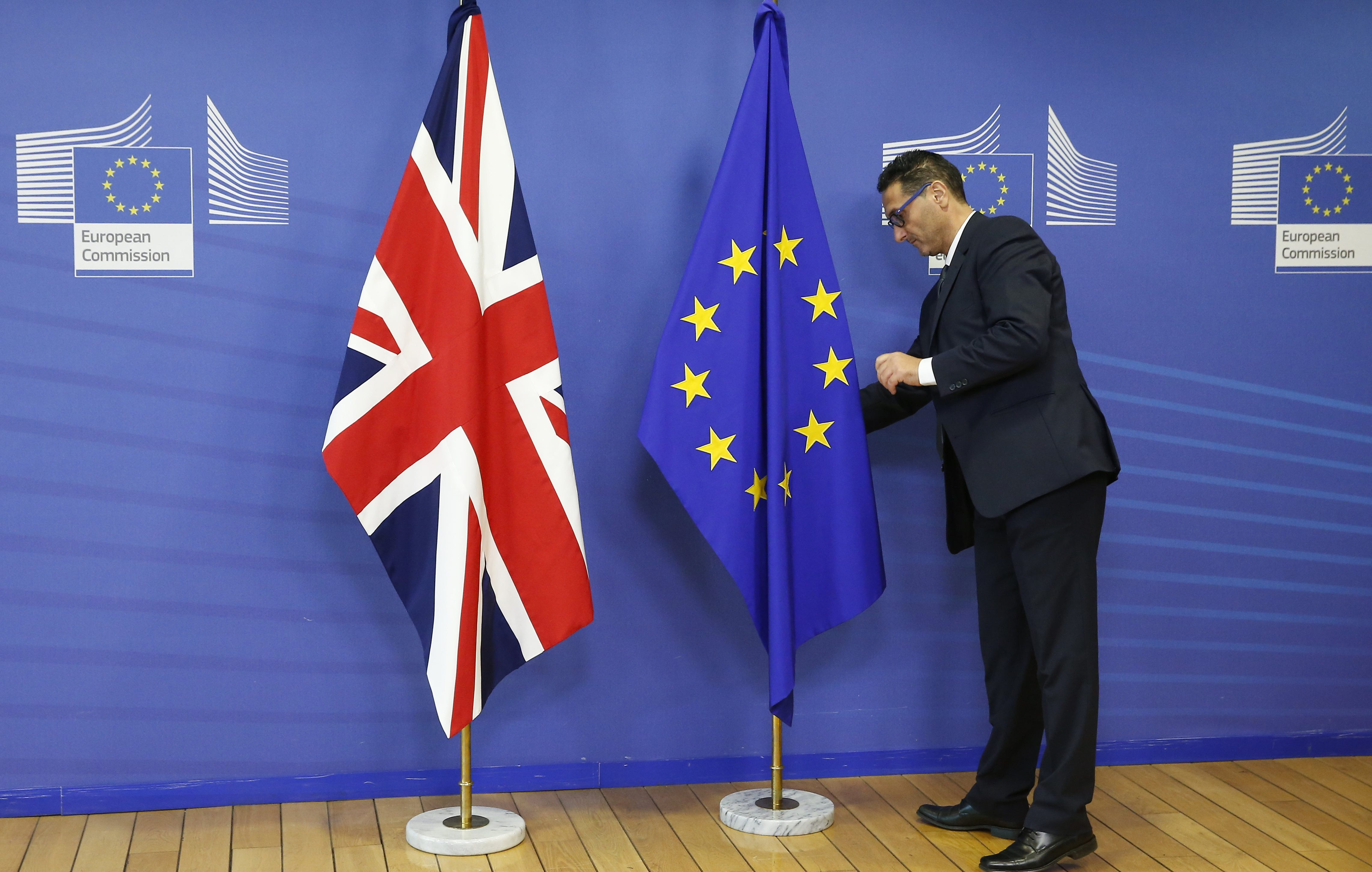 A employee of the EU Commission arranges the British Union flag and the European Union flag.