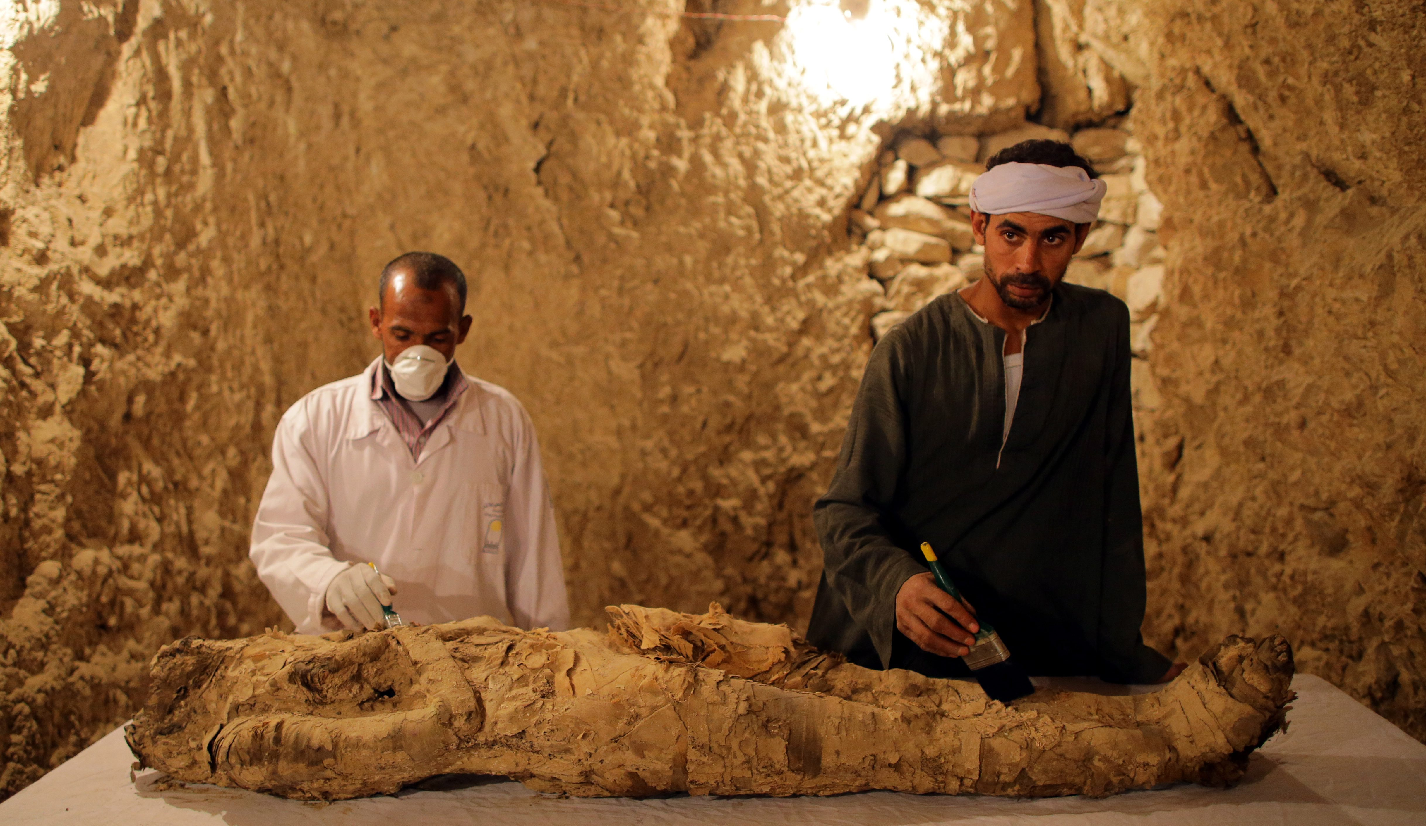 epaselect epa06378795 Egyptians archaeologists work on restoring a mummy at a recently found tomb and re-discovery of an older one, at Draa Abul Naga necropolis on Luxor?s west bank, 700km south of Cairo, Egypt, 09 December 2017. Egypt's Ministry of Antiquities announced the discovery of a tomb from the New Kingdom that belongs to the old Egyptian deity Amun's Goldsmith, Amenemhat (tomb number Kampp 390) and a burial shaft housing the mummy of a lady and her two children. The newly discovered tomb includes an entrance located in the courtyard of another Middle Kingdom tomb number Kampp 150.