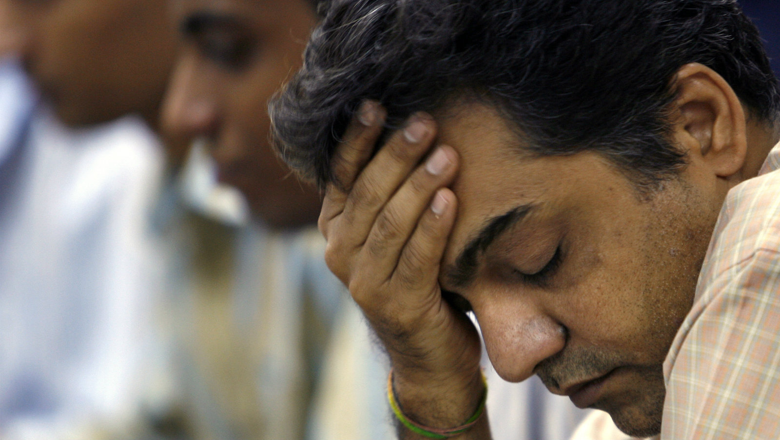 A stockbroker reacts during a trading session at a brokerage in Mumbai