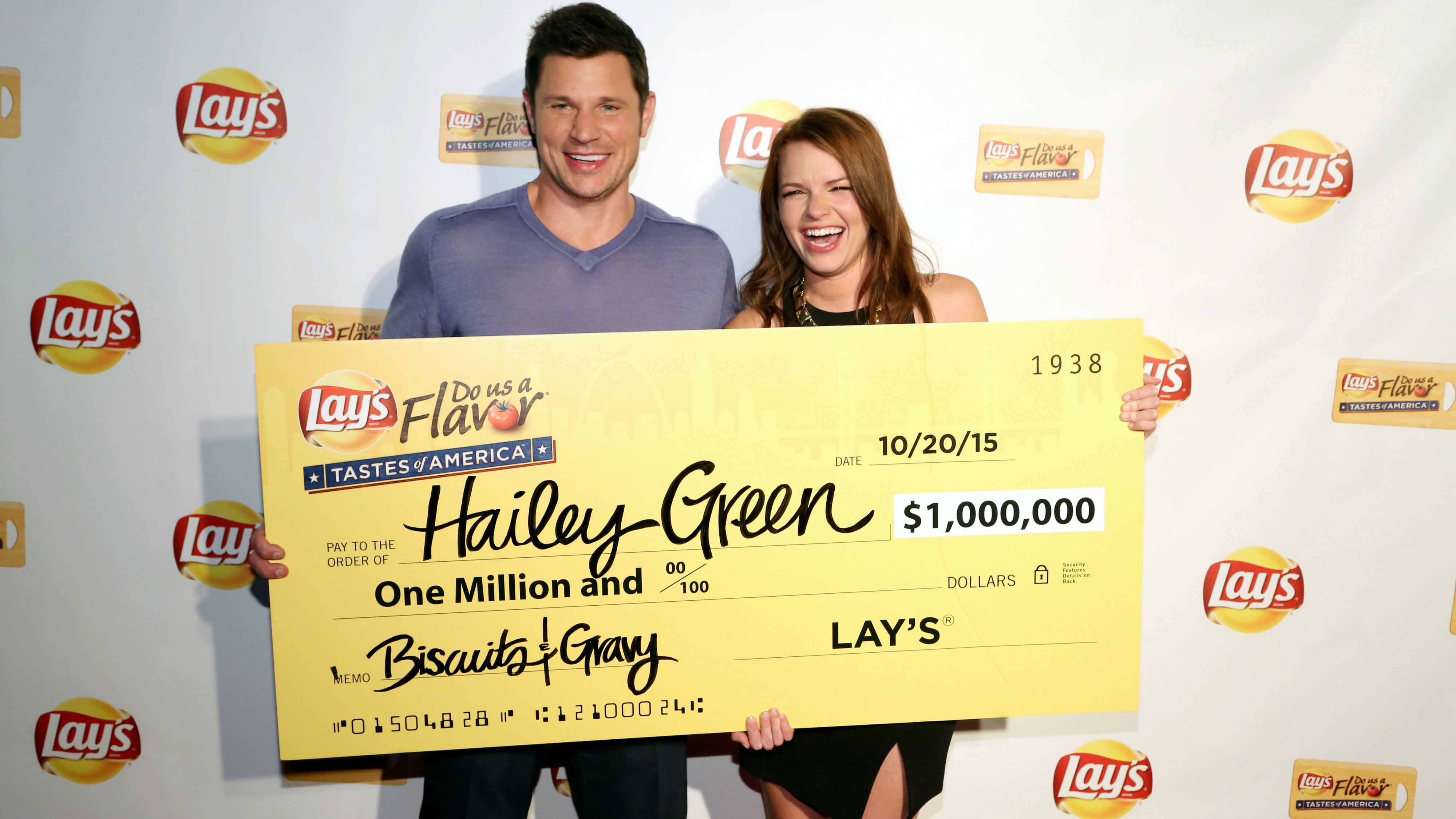 A woman and man hold a one million dollar check.