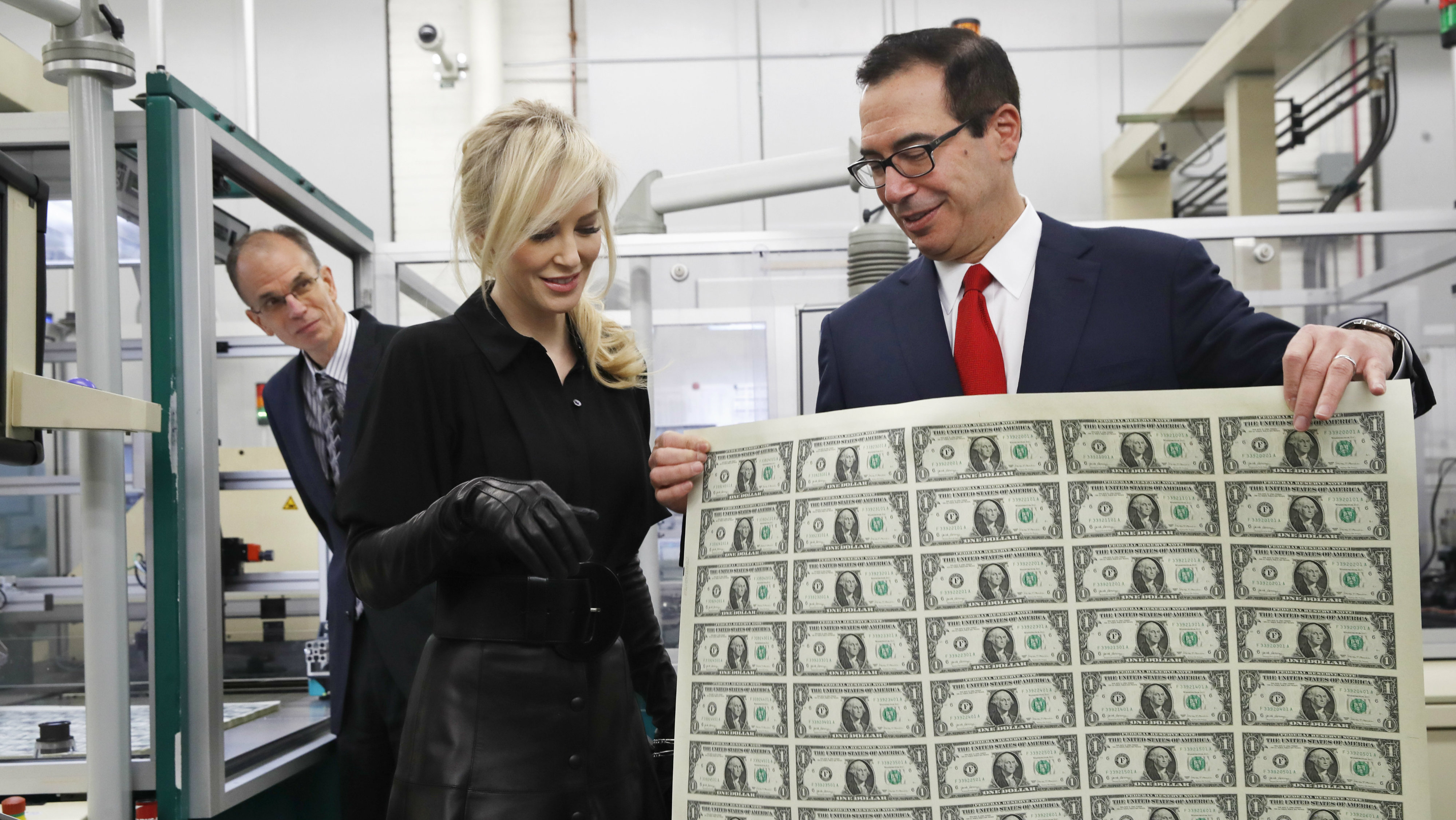 Treasury Secretary Steven Mnuchin, right, shows his wife Louise Linton a sheet of new $1 bills