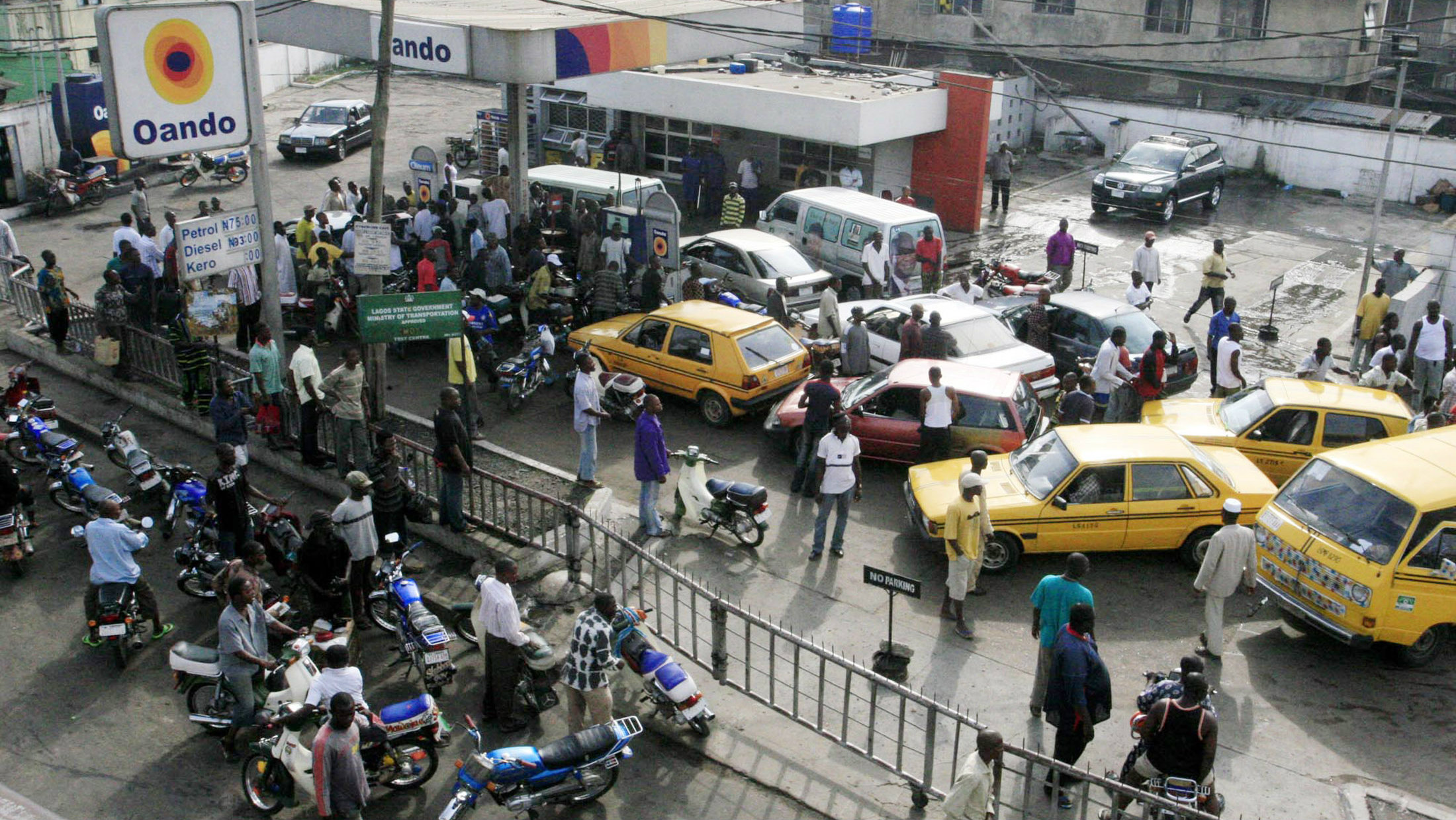 People wait with their vehicles to buy petrol at a fuel station in Nigeria's commercial capital Lagos, June 17, 2007. A strike by fuel tanker drivers, which was in its fourth day on Sunday, has caused the fuel scarcity across Africa's top oil producer and is a prelude to an indefinite general strike due to start on Wednesday in the world's eighth largest oil exporter. The strike is to protest against rising prices and privatisations.