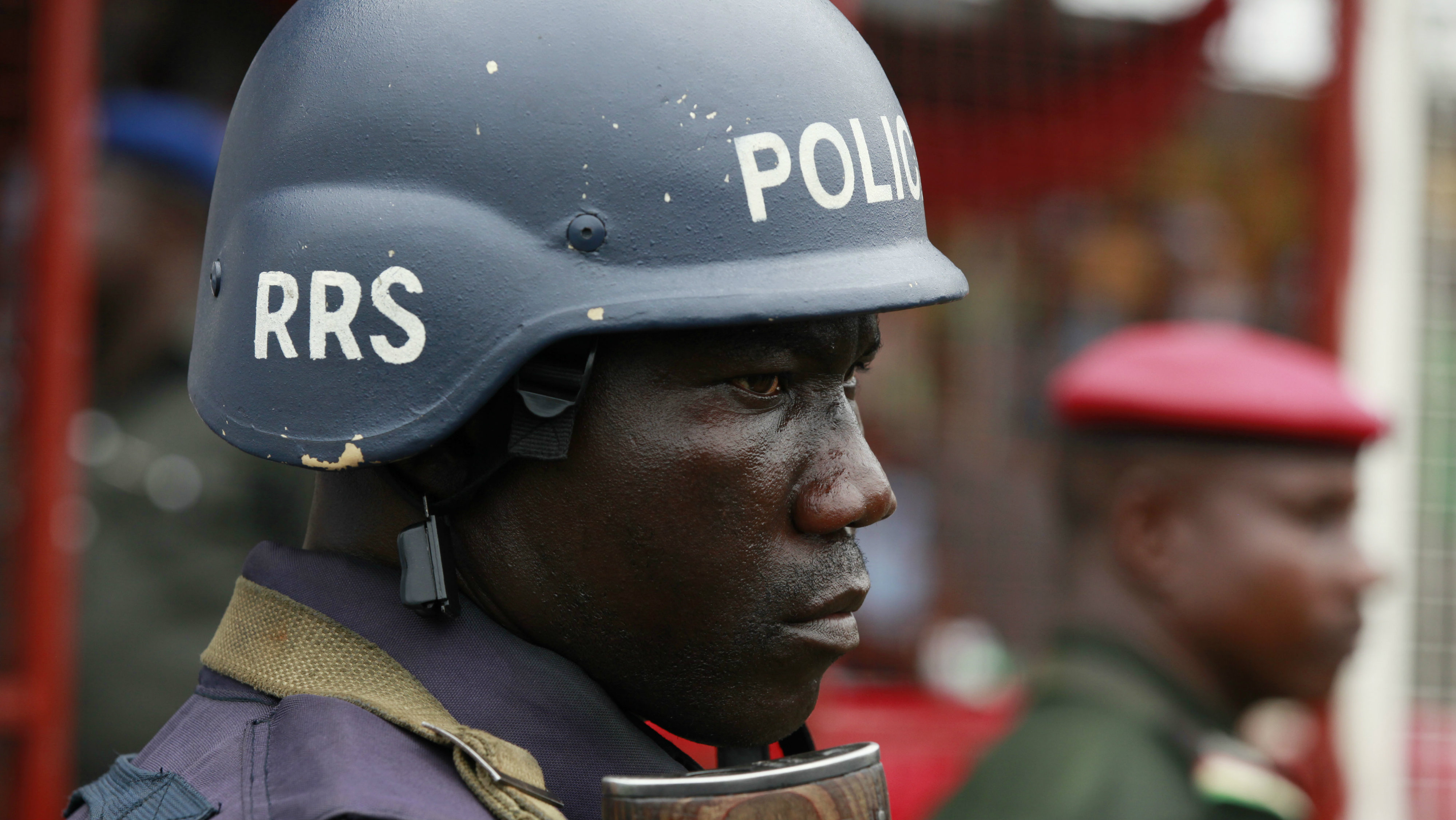 In this Thursday, May. 1, 2014 file photo, a police officer stand guards during a demonstration in Lagos, Nigeria. An elite Nigerian police squad set up to combat violent crime is torturing detainees to extract lucrative bribes and confessions, Amnesty International said in a report published Wednesday Sept. 21, 2016. The report says the Special Anti-Robbery Squad demands bribes, steals and extorts money from criminal suspects and their families.