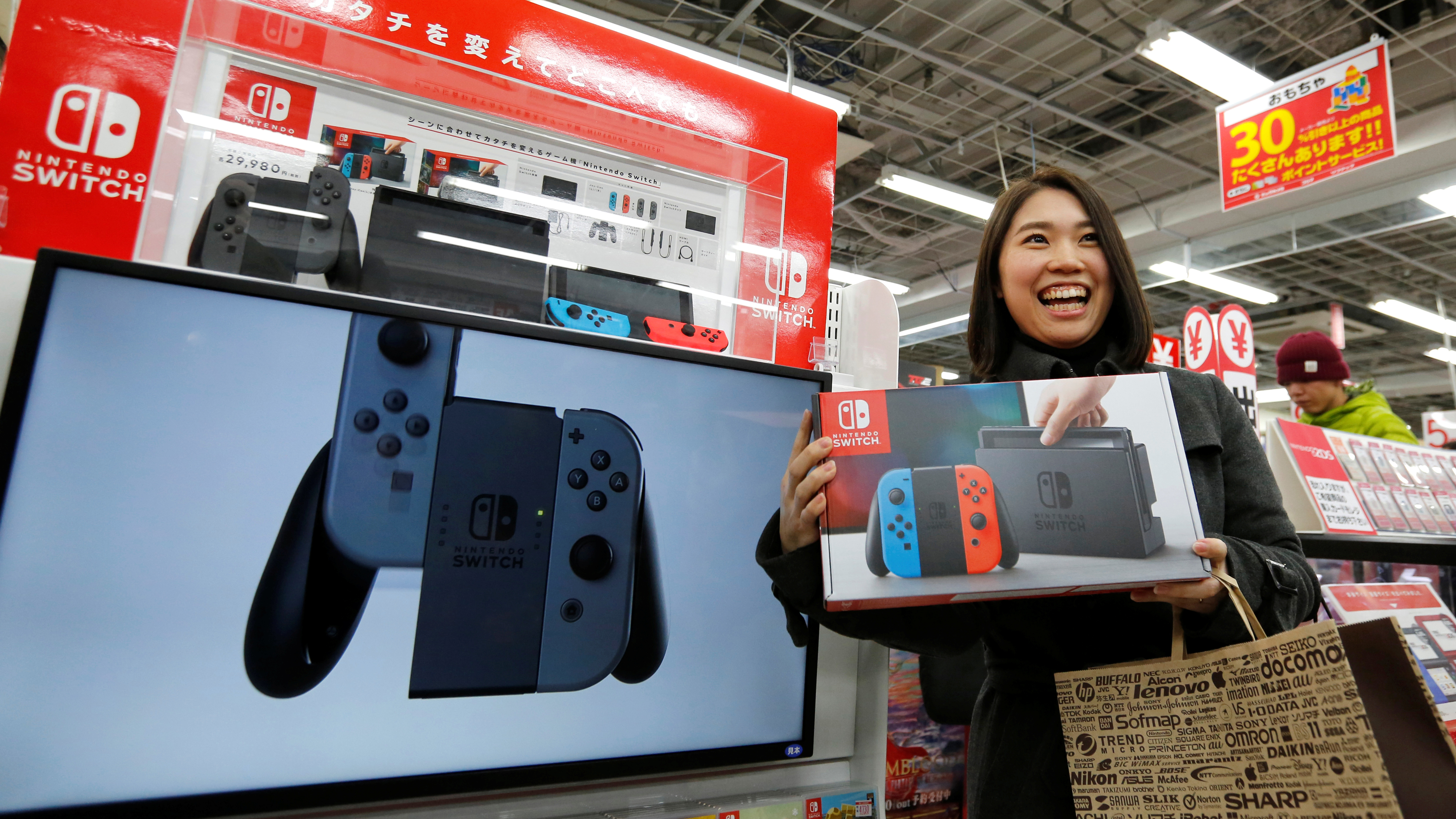 Nao Imoto smiles as she poses with her Nintendo Switch game console after buying it at an electronics store in Tokyo, Japan March 3, 2017.  REUTERS/Toru Hanai - RC1A26499830
