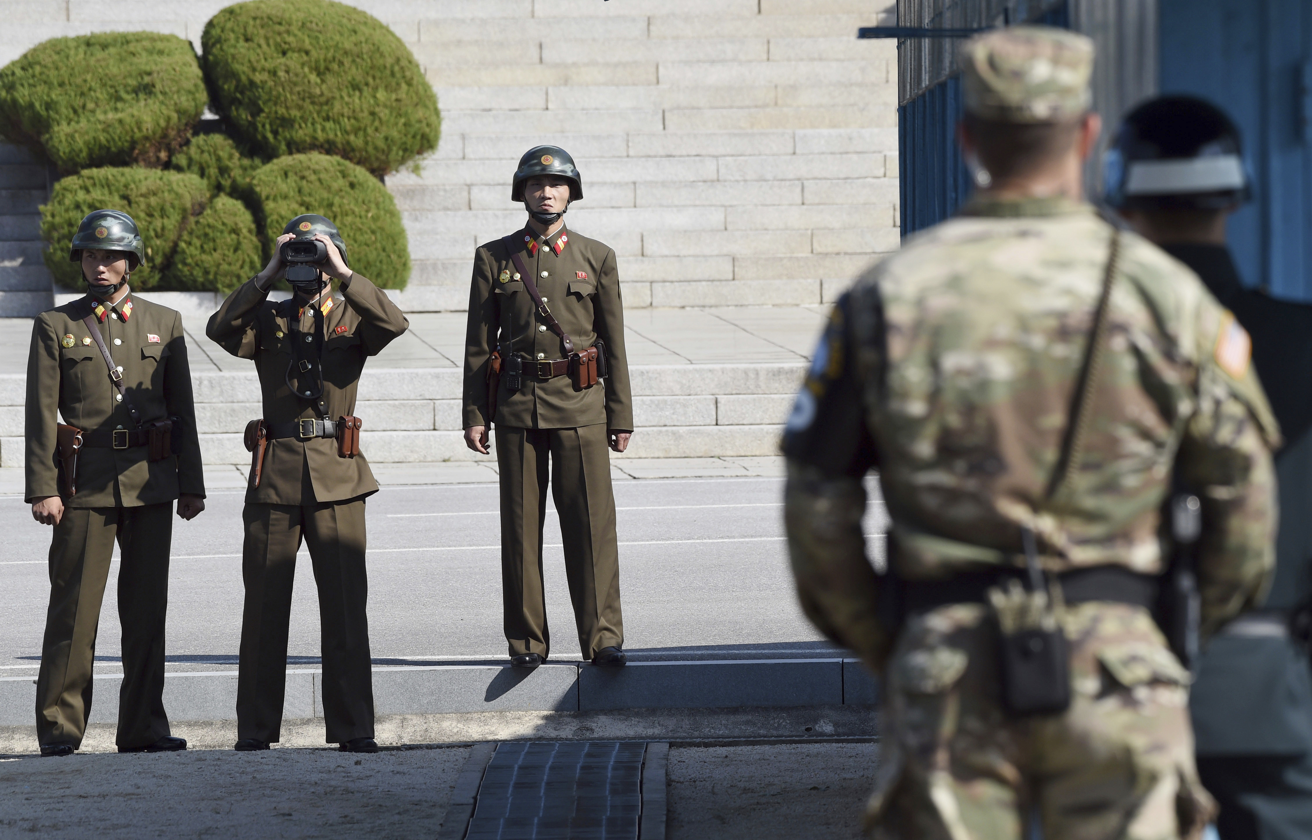 North Korean soldiers, left, look at the South side while U.S. Defense Secretary Jim Mattis and South Korean Defense Minister Song Young-moo visit the truce village of Panmunjom in the Demilitarized Zone (DMZ) on the border between North and South Korea Friday, Oct. 27, 2017. (Jung Yeon-je/Pool Photo via AP)