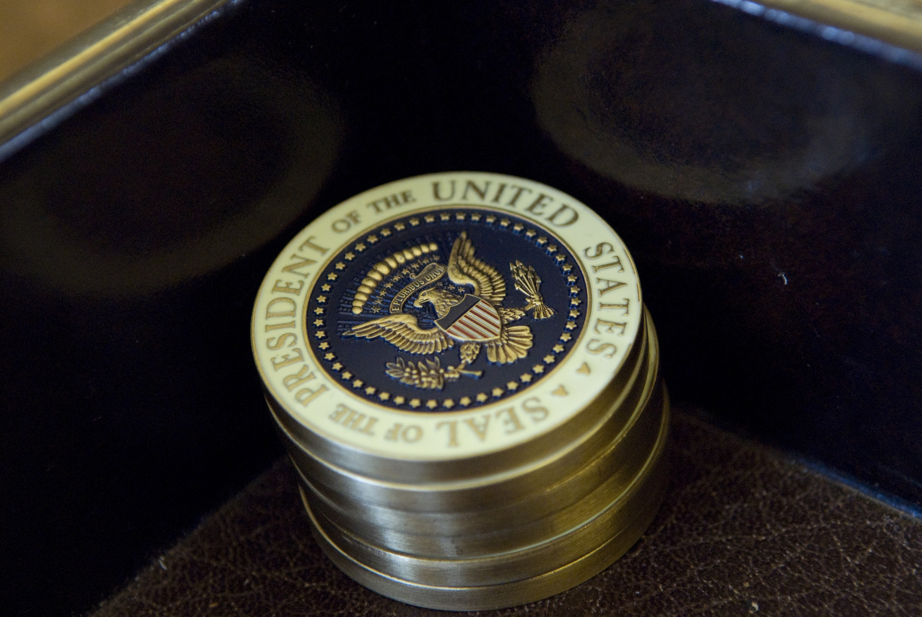 Challenge coins bearing the seal of the president sit on his desk in the Oval Office at the White House in Washington February 29, 2008.