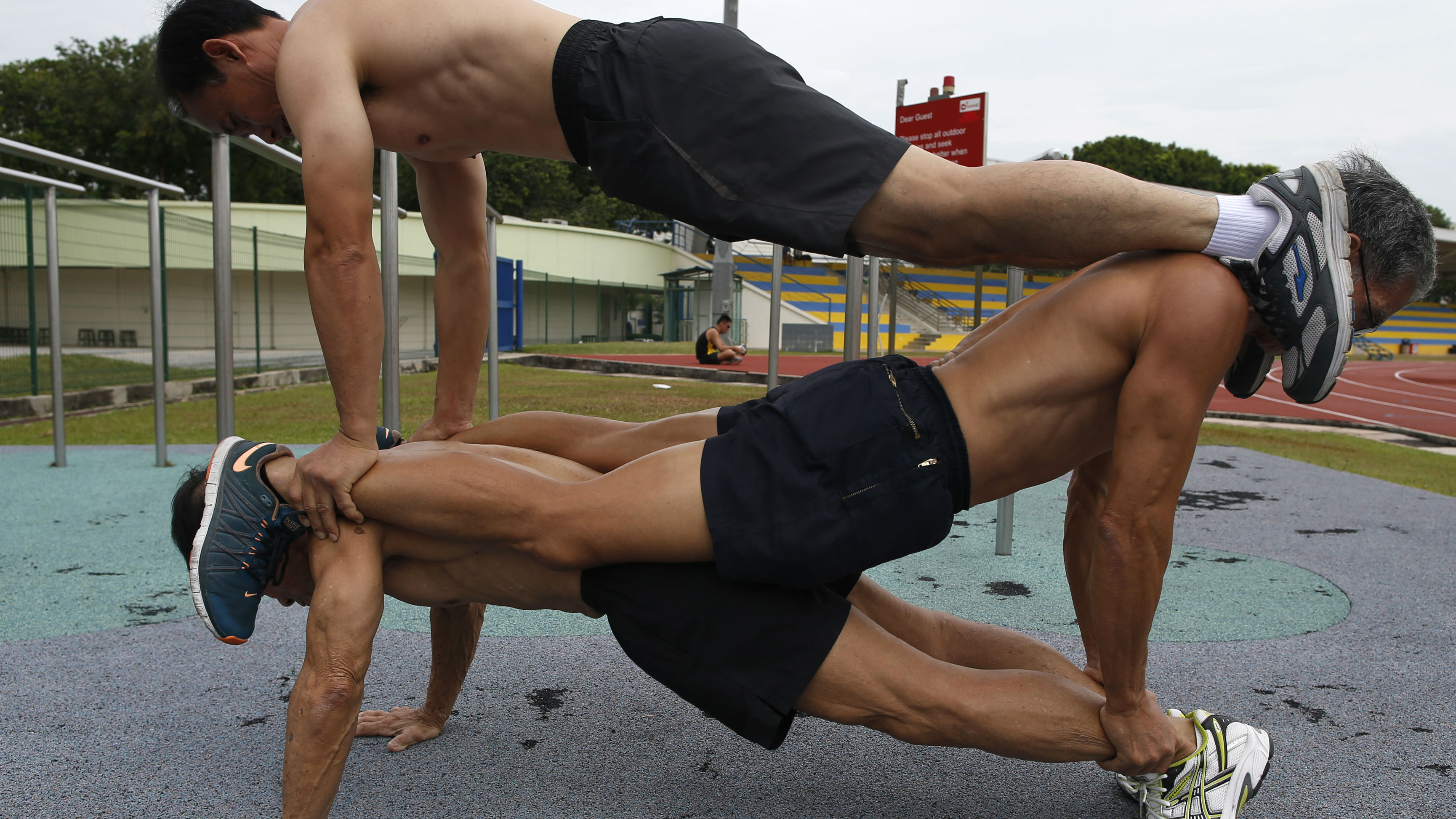 Three men doing plank pushups on each other.