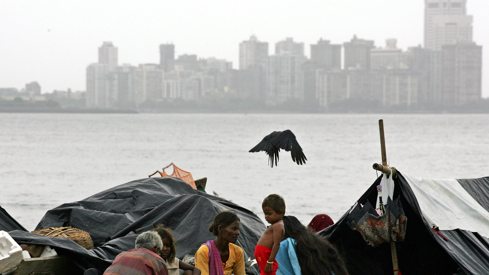 A homeless Indian family sits on a beach in Bombay August 4, 2005. India's share index rose to its ninth-straight closing high on Thursday, boosted by a major asset spin-off by Reliance Industries and robust foreign fund flows, as India's financial hub and film capital is gradually returning to normal life after a devastating flood killed nearly 1000 people and wreaked havoc on the city's rail, road and flight services.