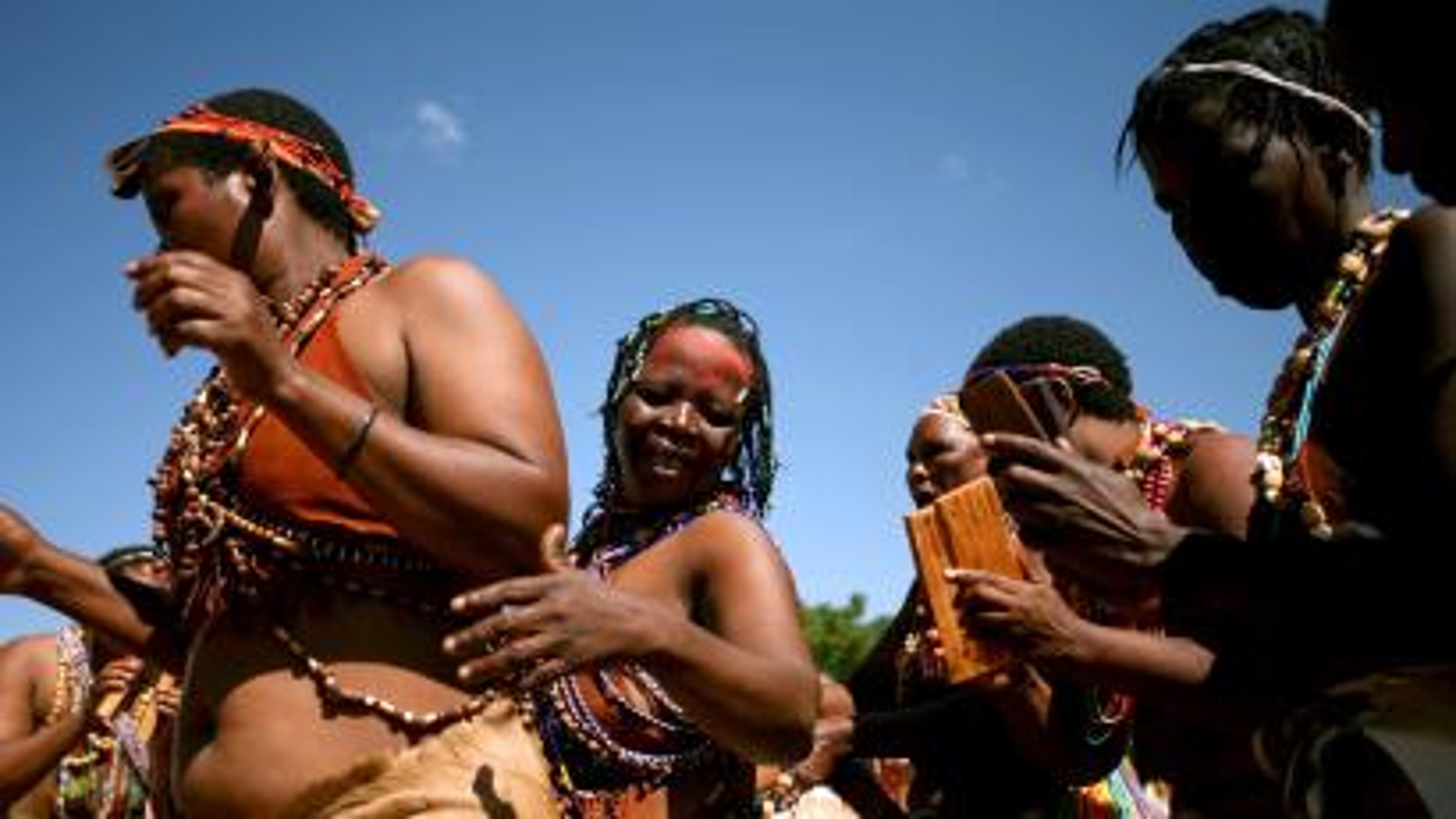 Women dressed in beaded animal skins perform celebratory dances.